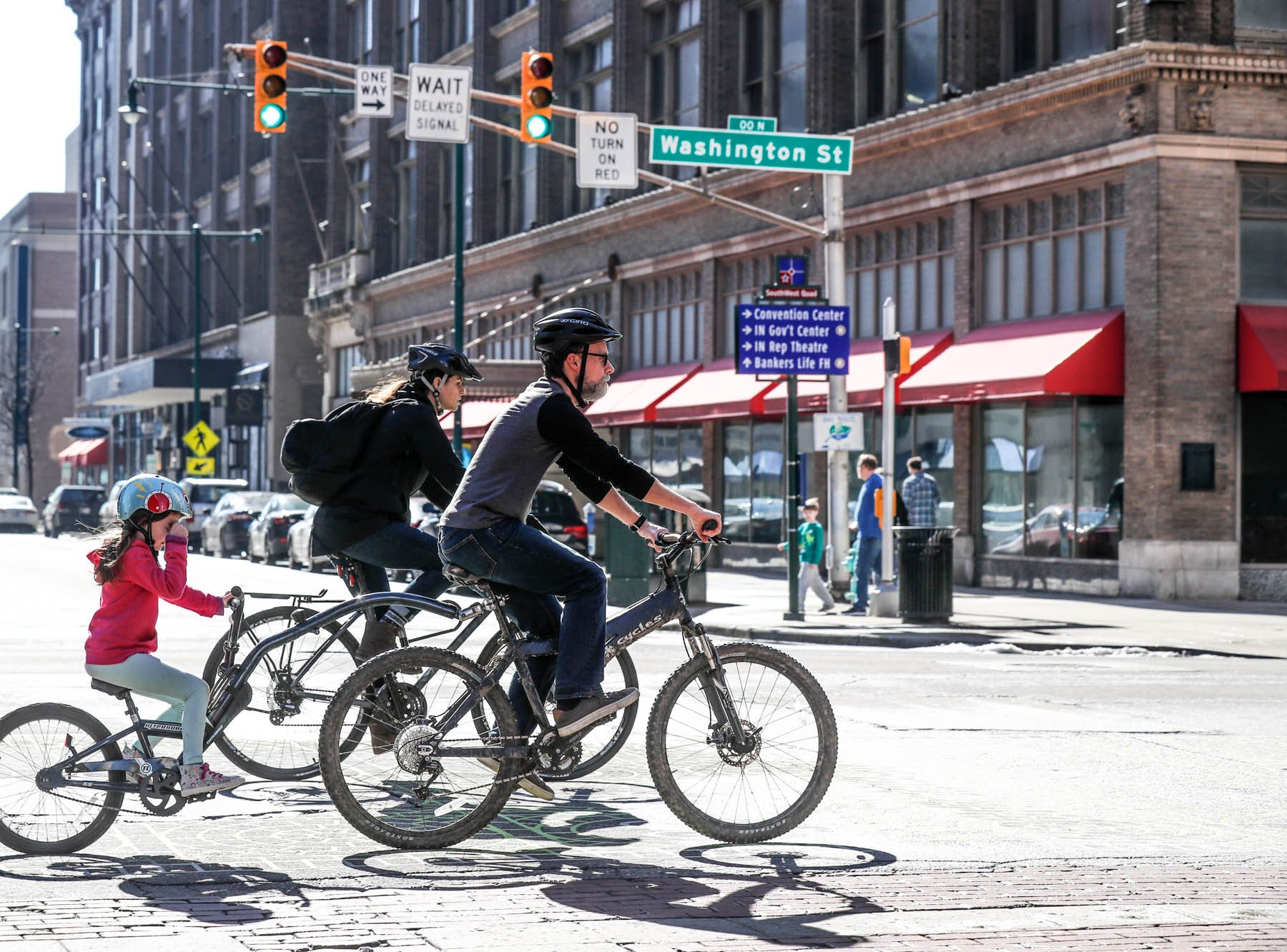 Cyclists ride through downtown on a near sixty-degree afternoon in Indianapolis on Sunday, Feb. 3, 2019.