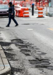 Potholes are seen on Meridian Street at 22nd Street, in Indianapolis, Thursday, Jan. 24, 2019.