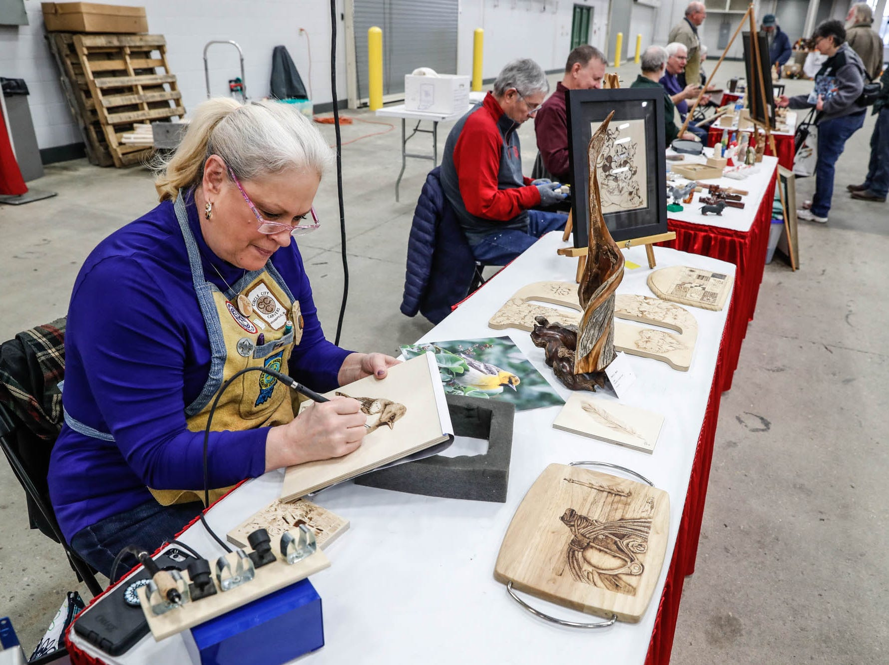 Wood worker Sherry Beck creates a wood burning portrait of a bird during a Wood Working Show at the Indiana State Fairgrounds in Indianapolis on Sunday, Feb. 3, 2019.