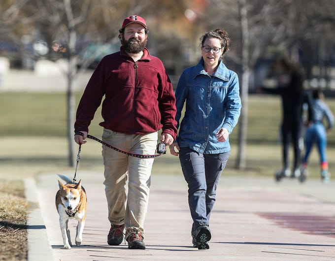 Collin Maher, Katie Polemis and dog Penny enjoy a 65-degree walk at White River State Park in Indianapolis, Sunday, Feb. 3, 2019. The warm weather comes just days after sub-zero temperatures swept over Indiana.