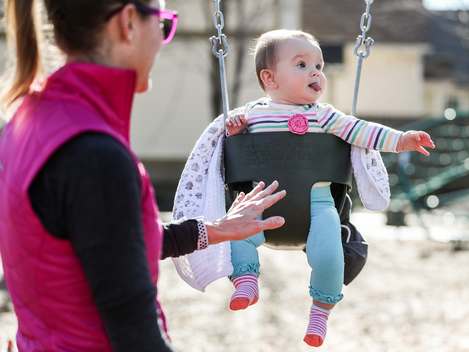 From left, Emily Cochard pushes her 8-month-old daughter Everly Monaghan, who looks to her father Mike Monaghan (not pictured), on the swings at Craig Kids Memorial Park in Indianapolis, Sunday, Feb. 3, 2019. The day's 65-degree weather comes just days after sub-zero temperatures swept over Indiana.