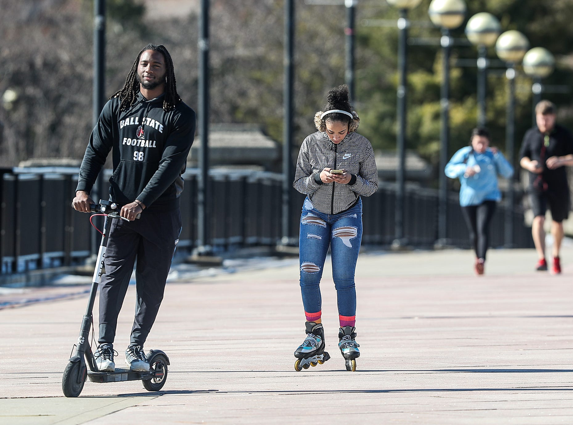 People skate, scooter, jog and walk on a 65-degree day at White River State Park in Indianapolis, Sunday, Feb. 3, 2019. The warm weather comes just days after sub-zero temperatures swept over Indiana.