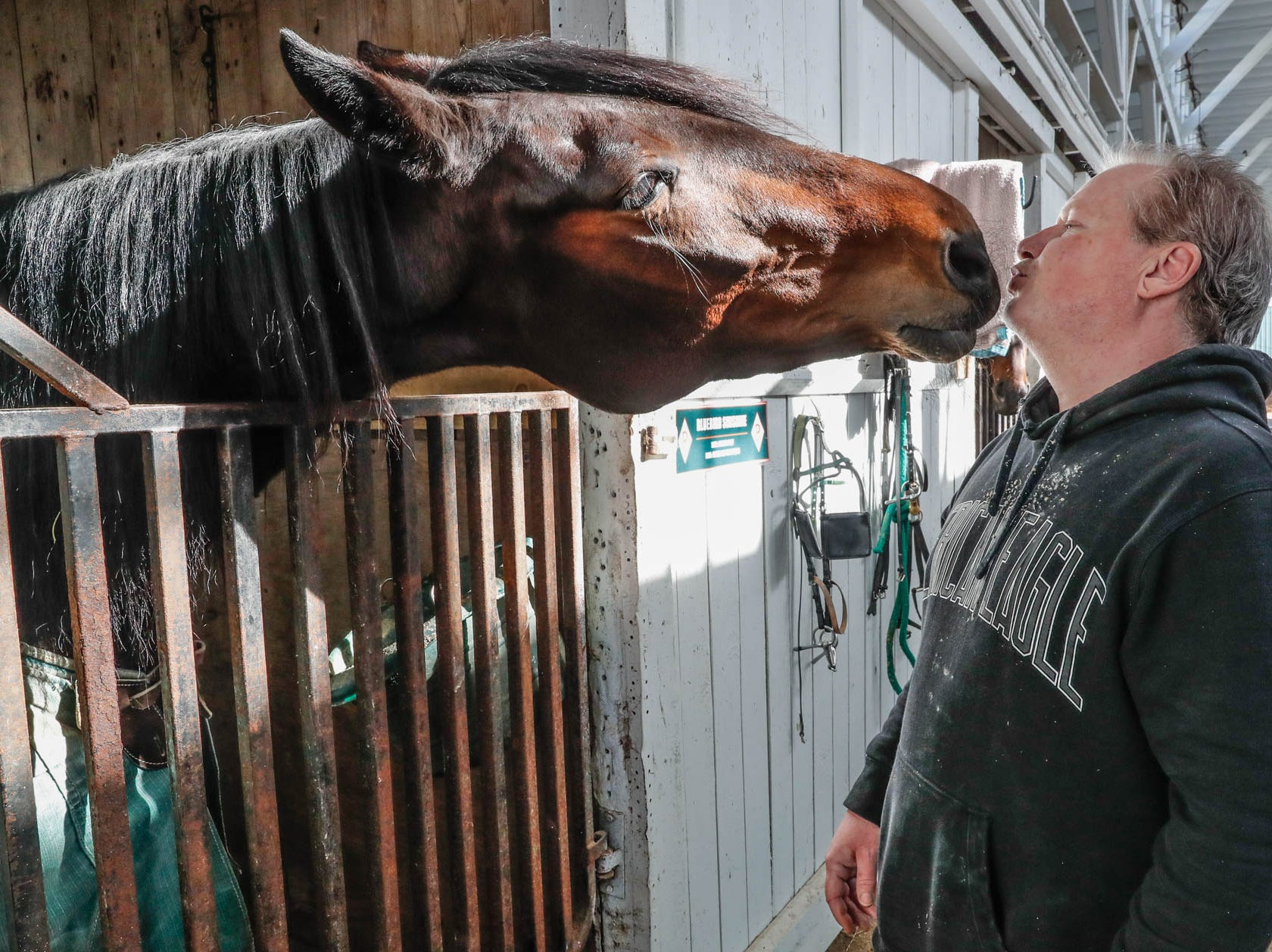 Mark P'Pool gets a kiss from his harness racing horse, Sunshine, inside the Mark P'Pool stables at the Indiana State Fairgrounds on Feb. 3, 2019.
