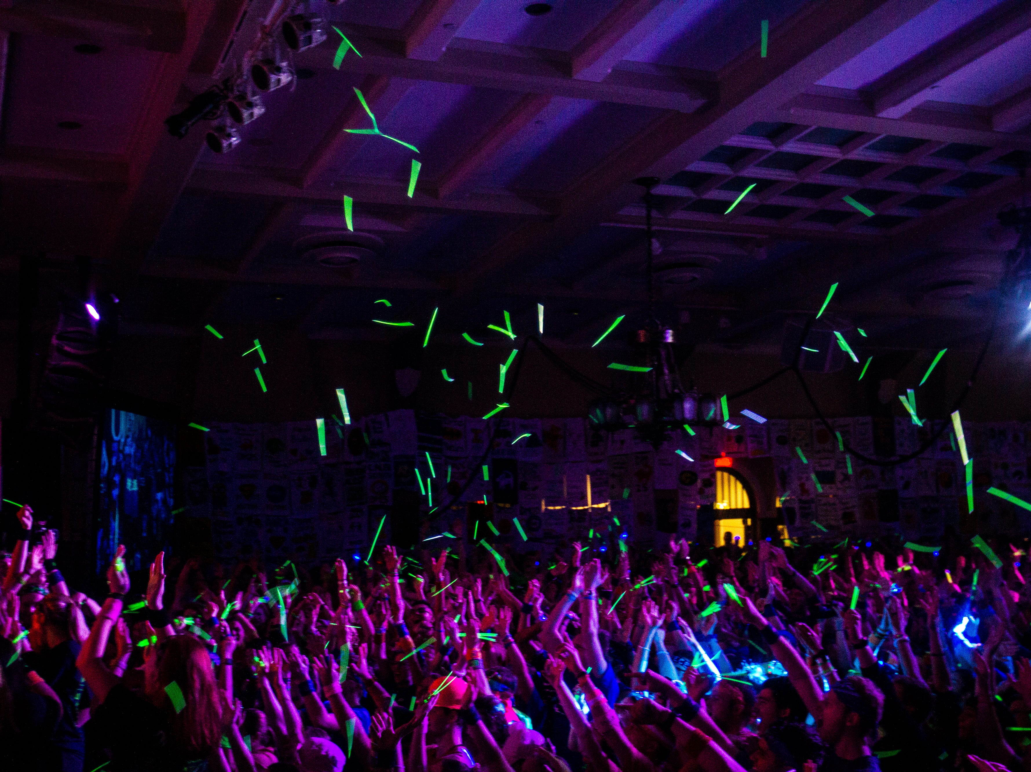 Students toss glow sticks in the air during the University of Iowa Dance Marathon 25 on Saturday, Feb. 2, 2019, at the Iowa Memorial Union in Iowa City, Iowa.