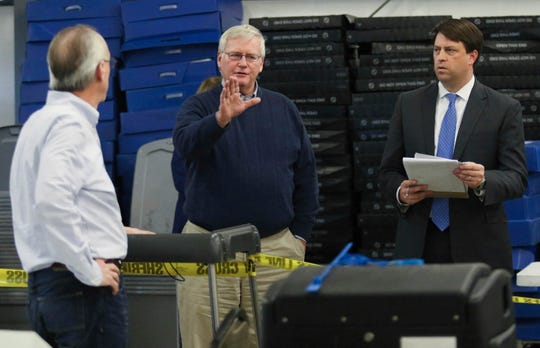 Kentucky 13th District House race candidate DJ Johnson, center, talks to election officials as Daviess County Attorney Claud Porter, left, looks on, and C. Michael Shull, III, a lawyer for Johnson, listens at right, during a recount of the Nov. 13, 2018 District House race at the Daviess County Operations Center in Owensboro, Ky., on Saturday, Feb 2, 2019. (Greg Eans/The Messenger-Inquirer via AP)