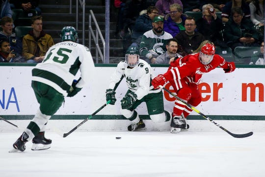 Michigan State's Mitch Lewandowski fights to get the puck to his linemate Patrick Khodorenko in Friday's 4-1 win over Wisconsin.