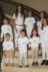 Members of the Greater Marco Family YMCA's swim team enjoy a photo in between welcoming guests to Hideaway Beach Club.
