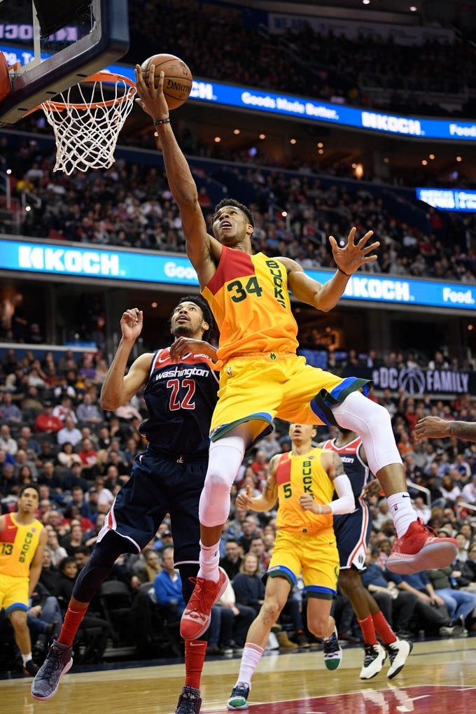 Giannis Antetokounmpo of the Bucks puts up a finger roll with his back to the basket during the second half against the Wizards on Saturday at Capital One Arena in Washington, D.C.