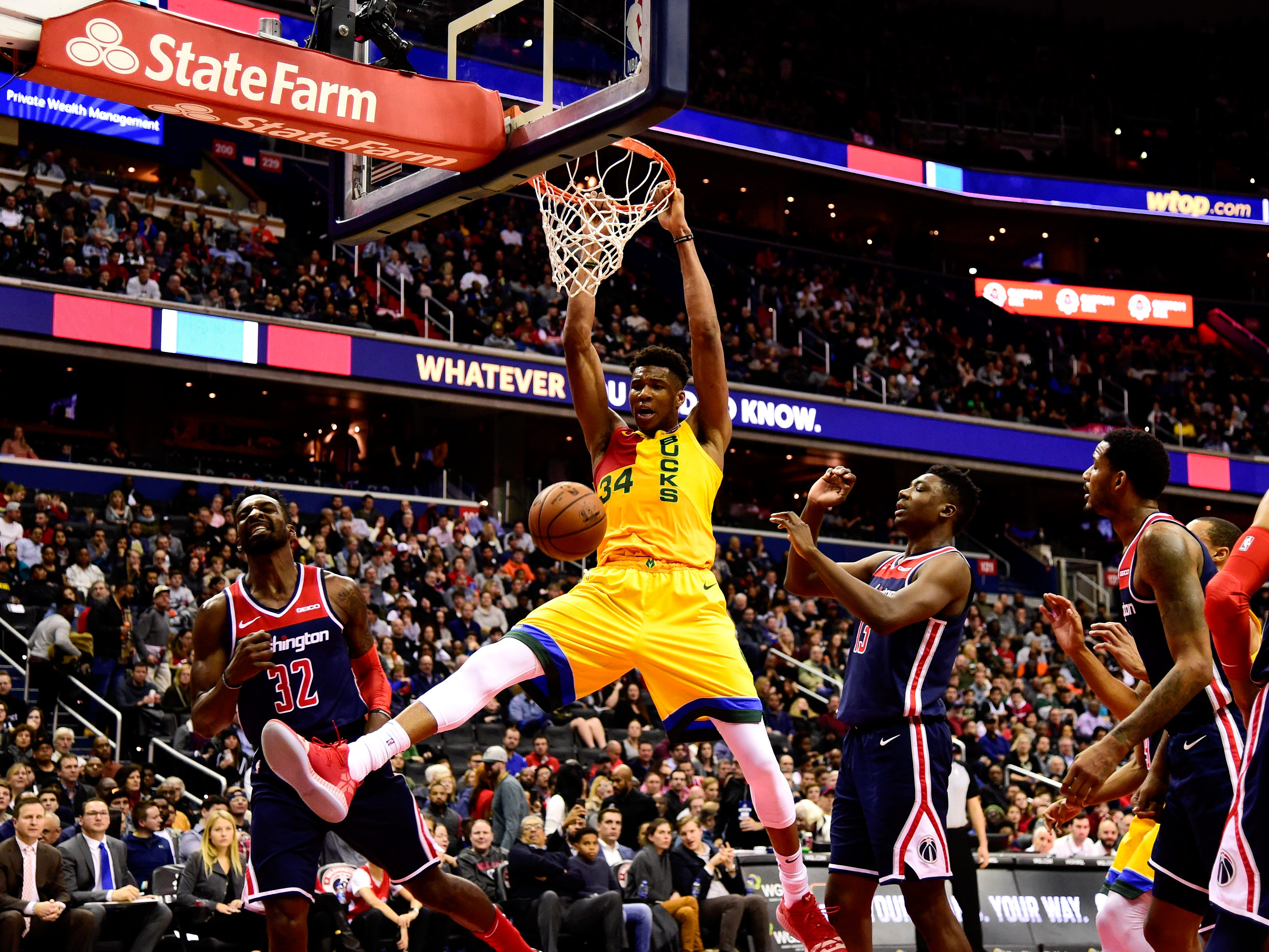 Giannis Antetokounmpo of the Bucks throws down a dunk as a quartet of Wizards players look on during the second quarter Saturday.