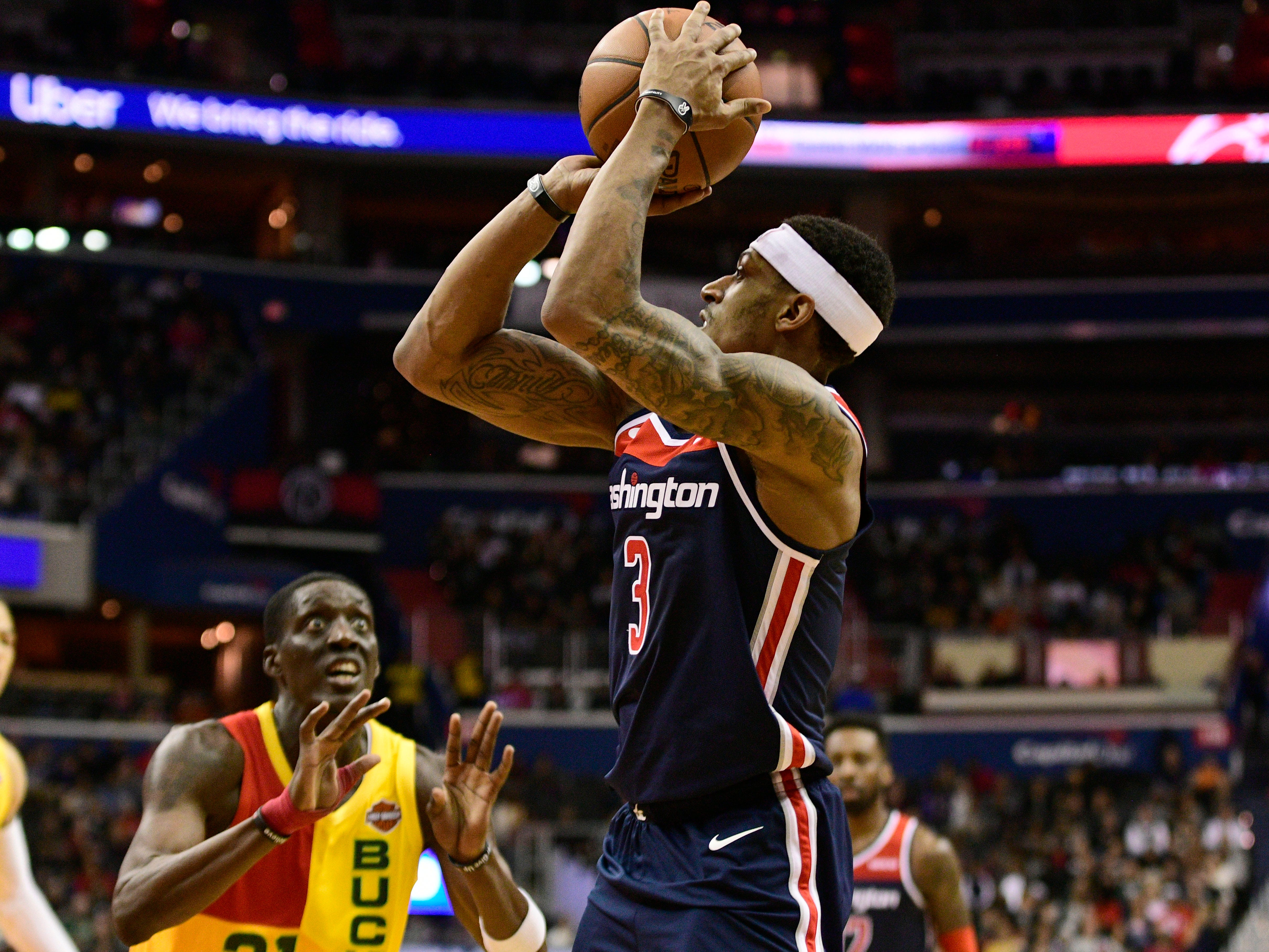 A bug-eyed Tony Snell of the Bucks watches as Bradley Beal of the Wizards shoots during the fourth quarter Saturday.