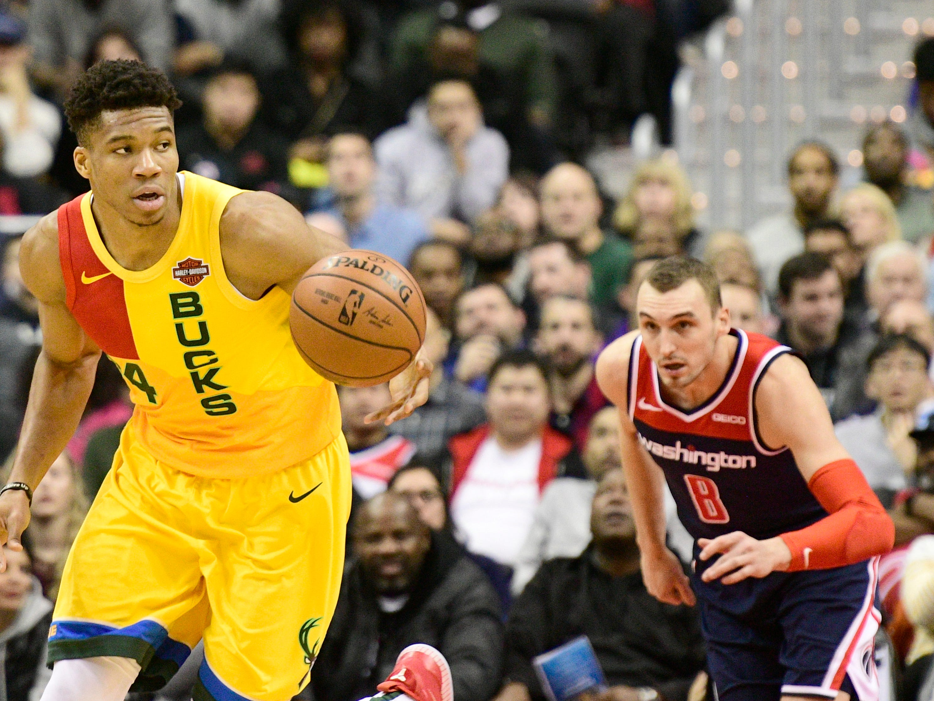 Bucks forward Giannis Antetokounmpo heads up the court with Wizards forward and former Wisconsin Badgers standout Sam Dekker trailing the play during the first quarter Saturday.
