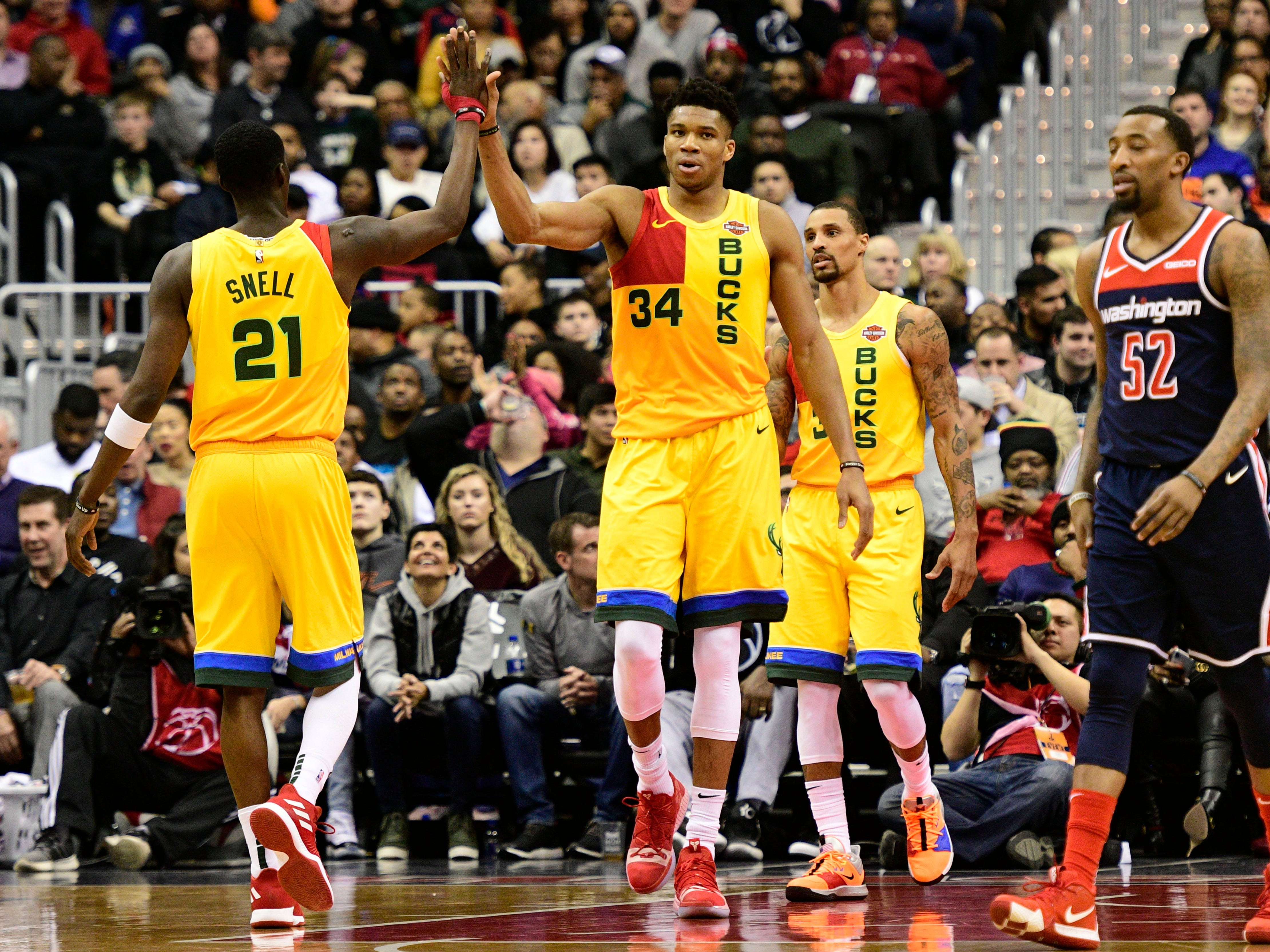 Giannis Antetokounmpo and Tony Snell of the Bucks high-five each other after the Greek Freak hit a shot while being fouled by a Wizards player in the second half Saturday.