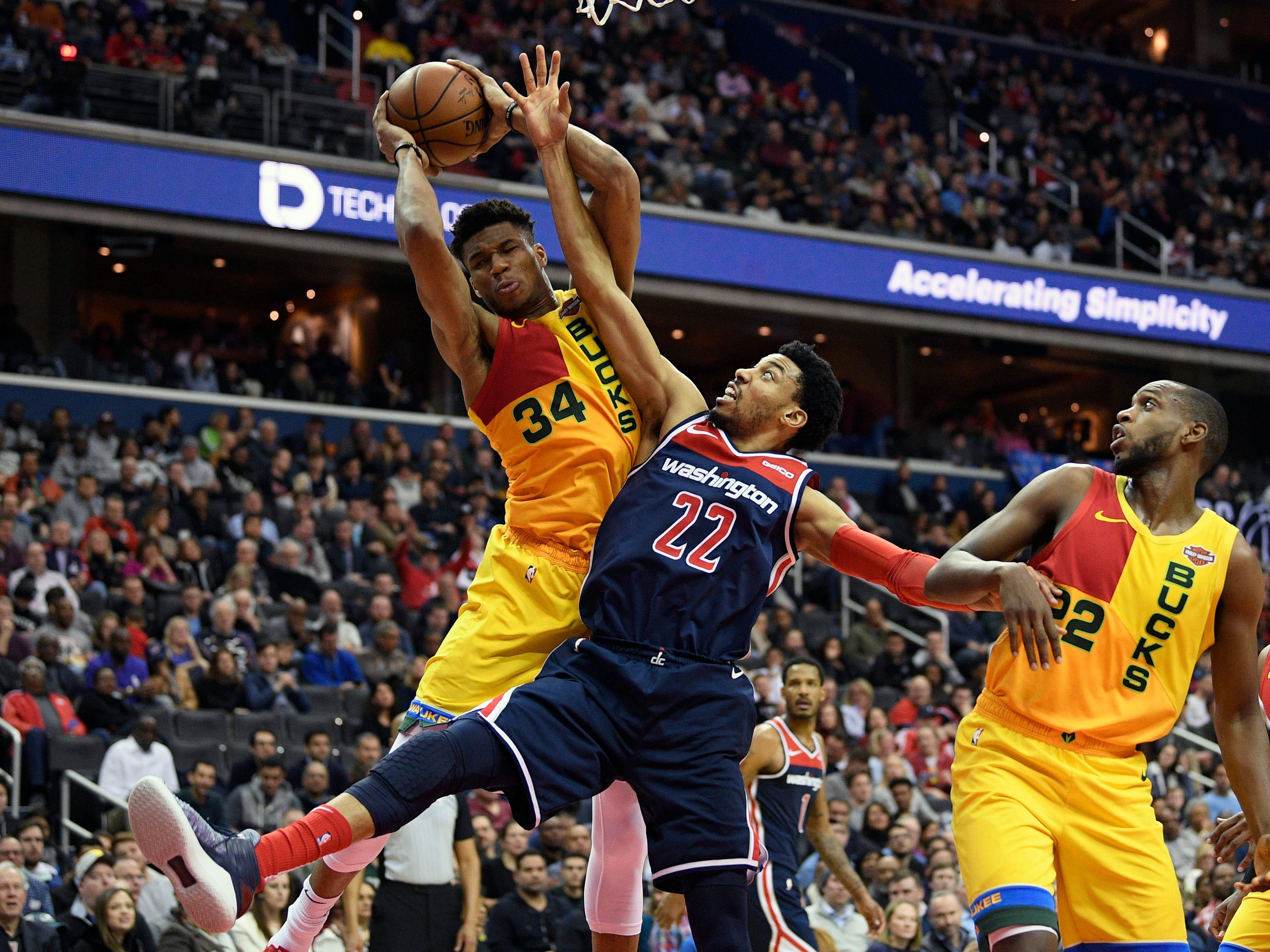 Bucks forward Giannis Antetokounmpo rips down a rebound against Wizards forward Otto Porter Jr. during the first half Saturday.