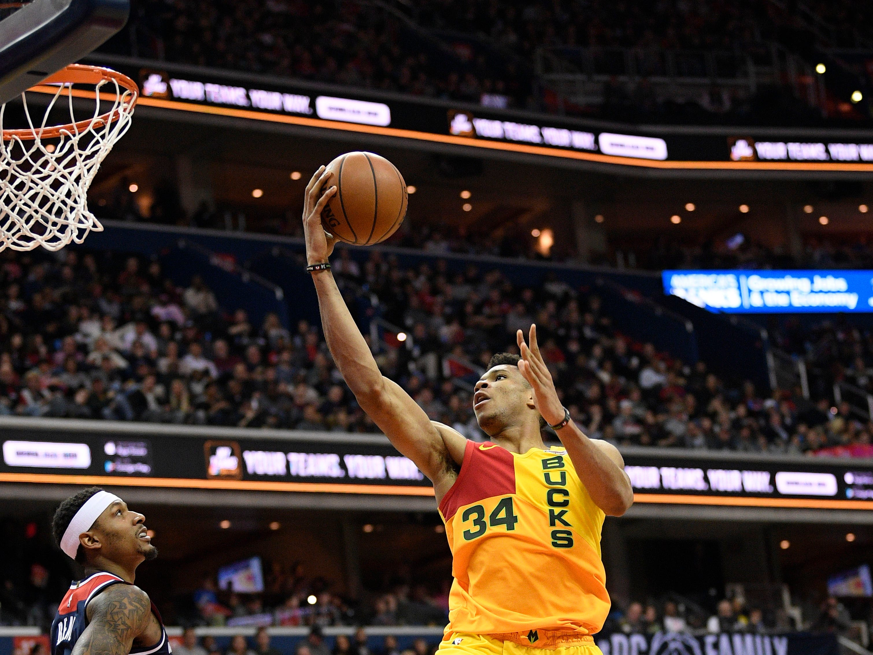 Bucks forward Giannis Antetokounmpo goes to the basket for a shot as Bradley Beal (left) of the Wizards basically stays out of his way during the second half Saturday night.