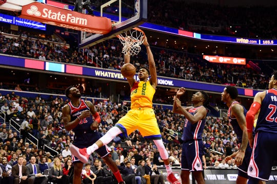 Bucks forward Giannis Antetokounmpo  dunks over Wizards forward Jeff Green on Saturday night in Washington.