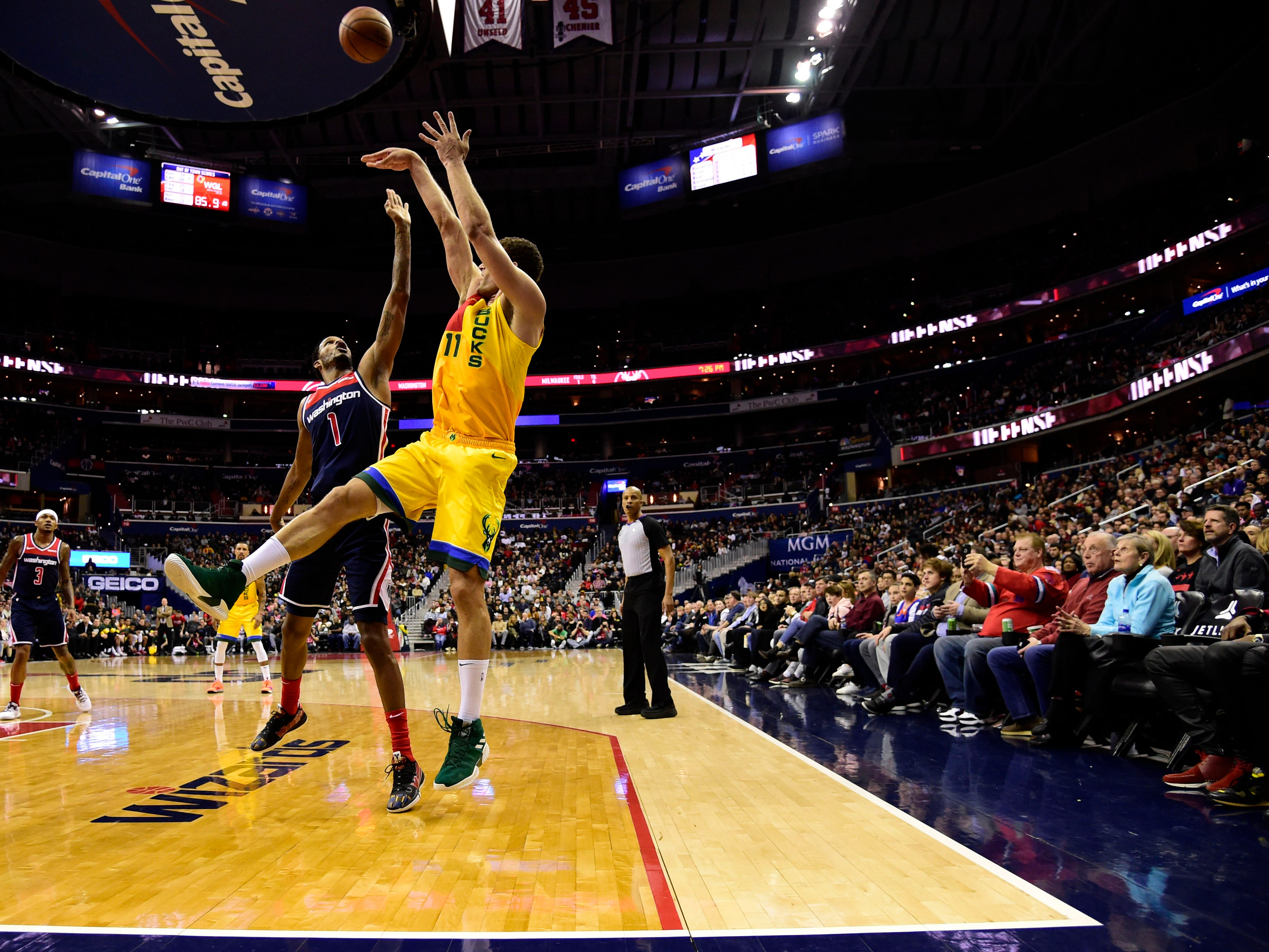 Bucks center Brook Lopez hoist up a shot from just inside the three-point line while being guarded by Wizards forward Trevor Ariza during the first half Saturday.
