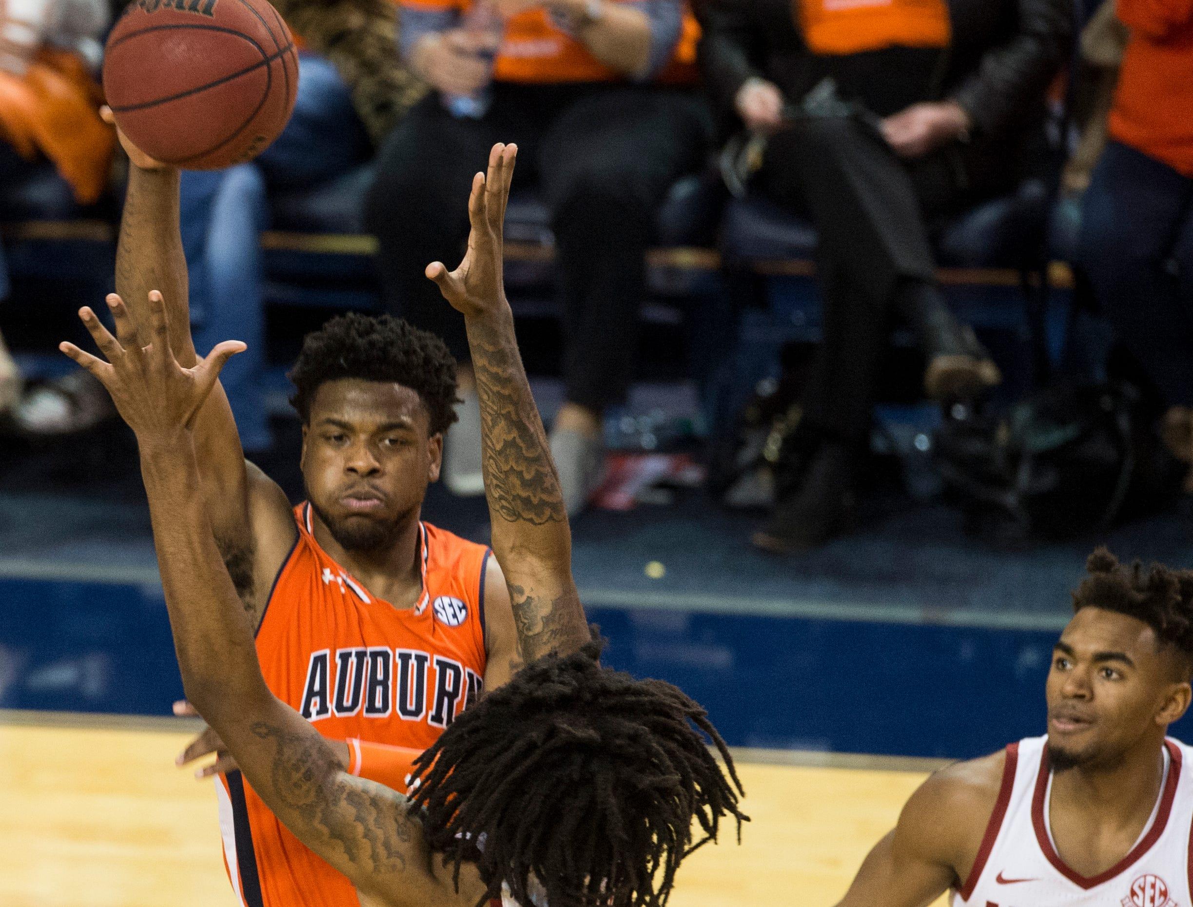 Auburn guard Malik Dunbar (4) passes the ball over Alabama guard John Petty (23) at Auburn Arena in Auburn, Ala., on Saturday, Feb. 2, 2019. Auburn defeated Alabama 84-63.