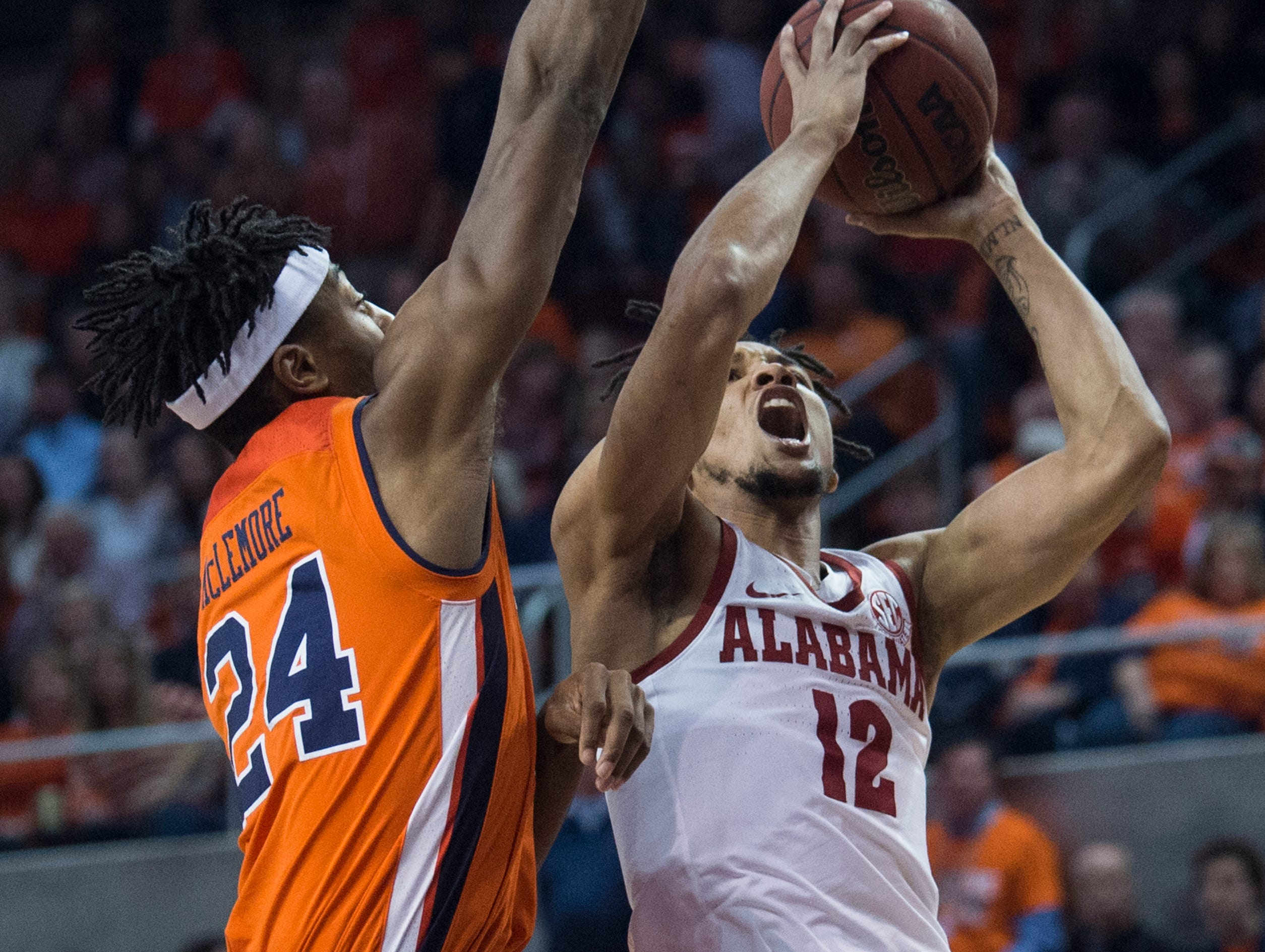 Alabama guard Dazon Ingram (12) goes up for a layup over Auburn forward Anfernee McLemore (24) at Auburn Arena in Auburn, Ala., on Saturday, Feb. 2, 2019. Auburn leads Alabama 48-28 at halftime.