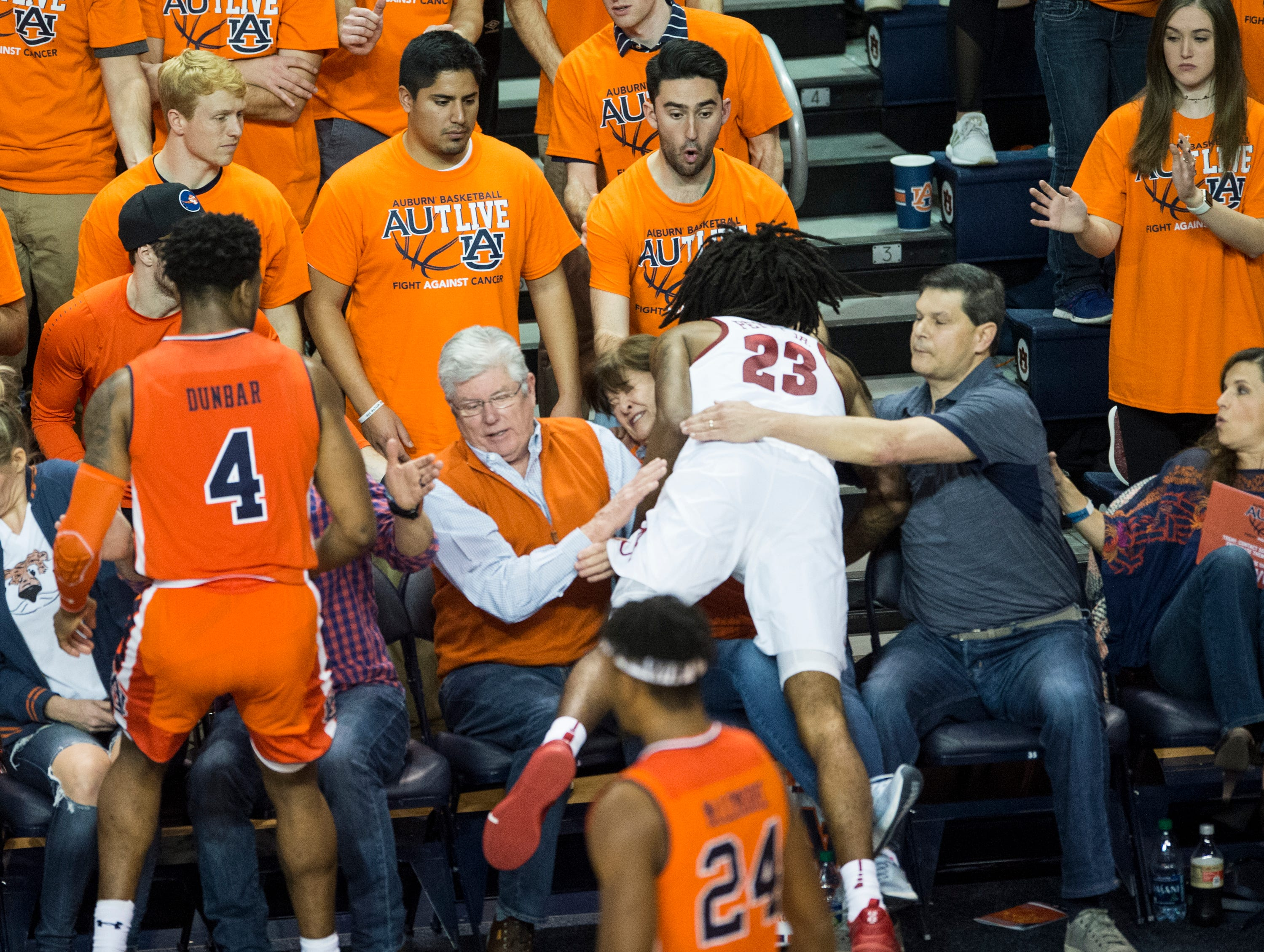 Alabama guard John Petty (23) lands on a fan as he attempts to save the ball at Auburn Arena in Auburn, Ala., on Saturday, Feb. 2, 2019. Auburn defeated Alabama 84-63.