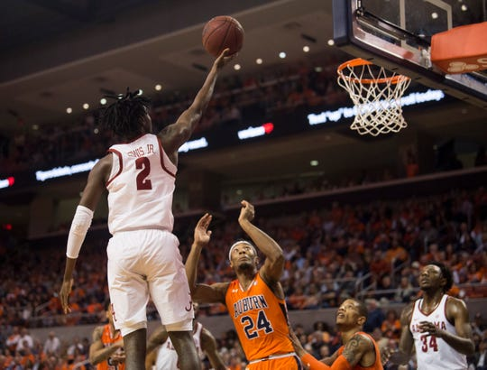 Alabama guard Kira Lewis Jr. (2) goes up for a layup over Auburn forward Anfernee McLemore (24) at Auburn Arena in Auburn, Ala., on Saturday, Feb. 2, 2019.