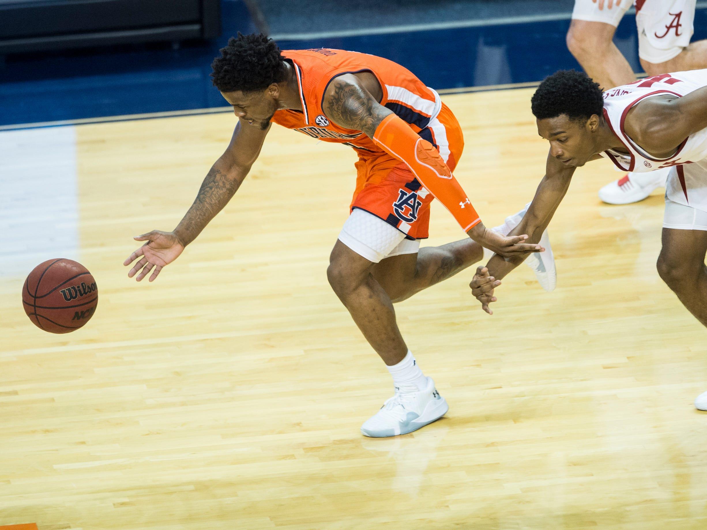 Auburn guard Malik Dunbar (4) and Alabama guard Herbert Jones (10) fight for a loose ball at Auburn Arena in Auburn, Ala., on Saturday, Feb. 2, 2019. Auburn defeated Alabama 84-63.
