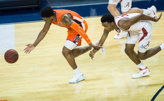 Auburn guard Malik Dunbar (4) and Alabama guard Herbert Jones (10) fight for a loose ball at Auburn Arena in Auburn, Ala., on Saturday, Feb. 2, 2019. Auburn defeated Alabama 84-63.