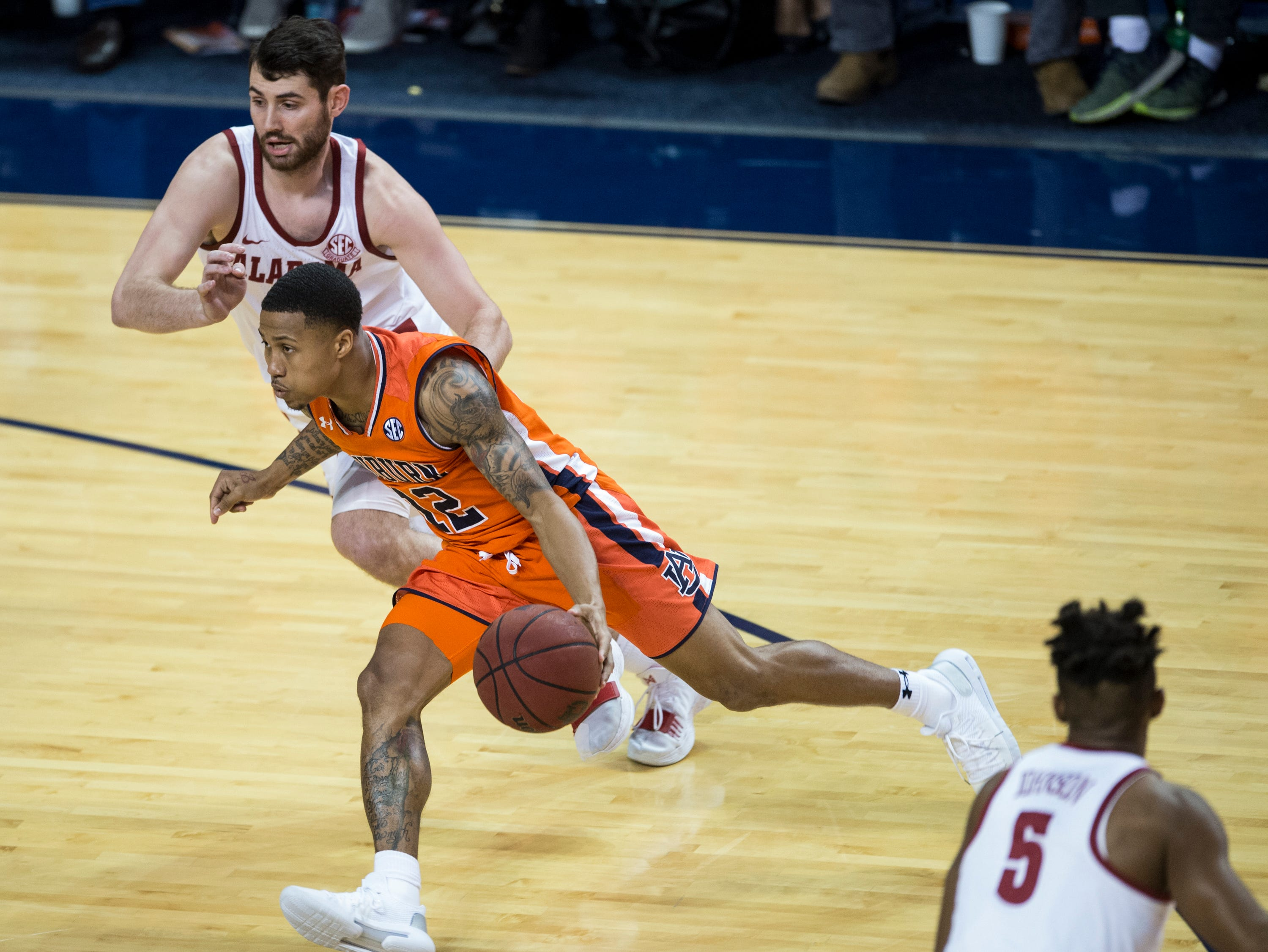Auburn guard J'Von McCormick (12) drives the ball on Alabama guard Riley Norris (1) at Auburn Arena in Auburn, Ala., on Saturday, Feb. 2, 2019. Auburn defeated Alabama 84-63.