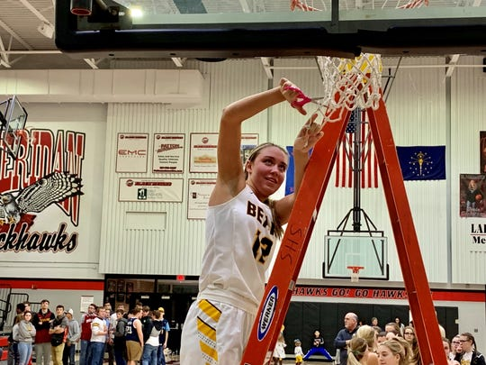 Monroe Central's Jordyn Barga cuts down the nets after the Golden Bears defeated Lapel for the Sheridan Sectional title.