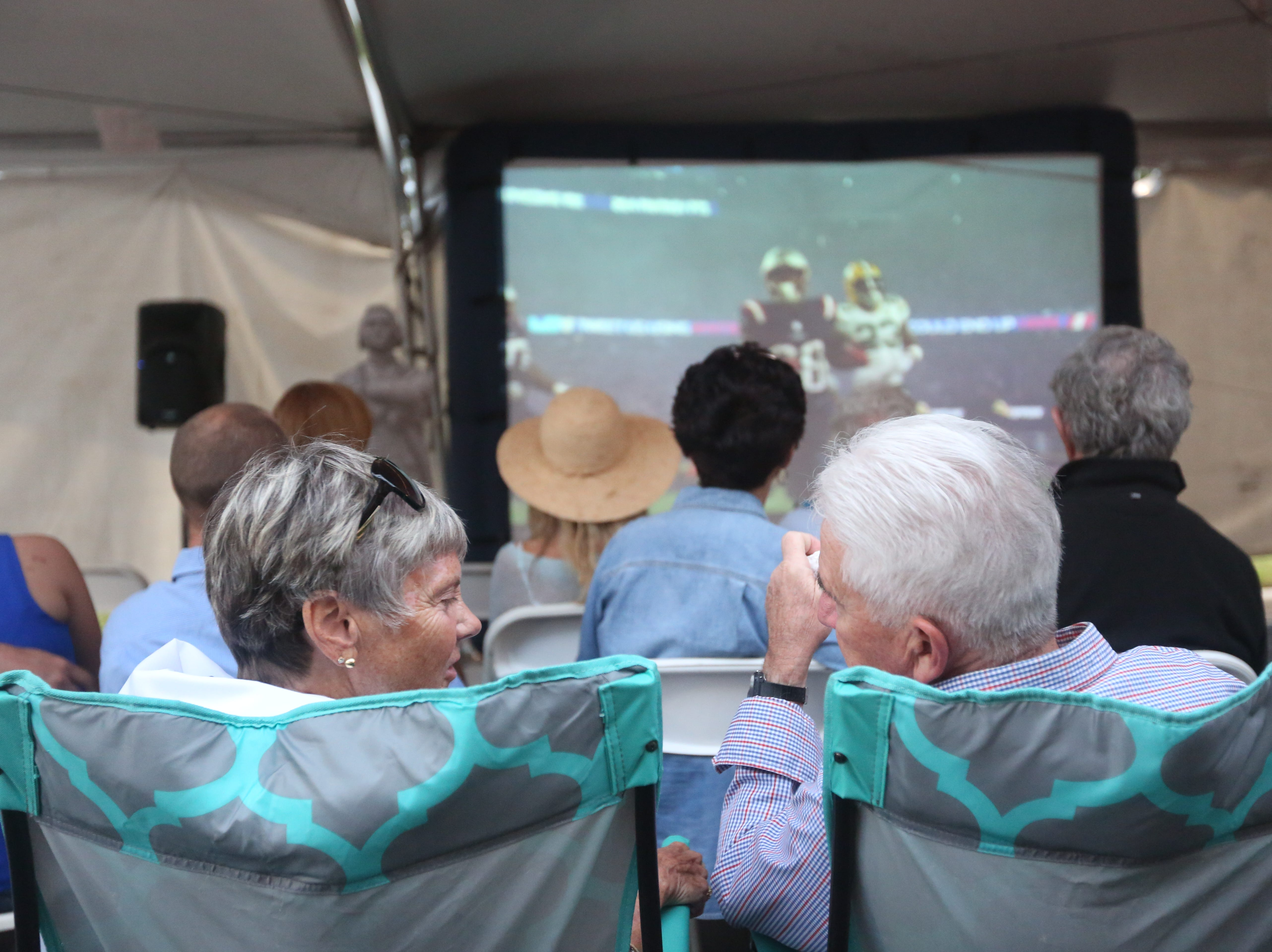 Molly and Glenn Ruoss, from Maine, watch the projected game in the large tent adjacent the Foxboro Sports Tavern in East Naples on Sunday, Feb. 3, 2019.