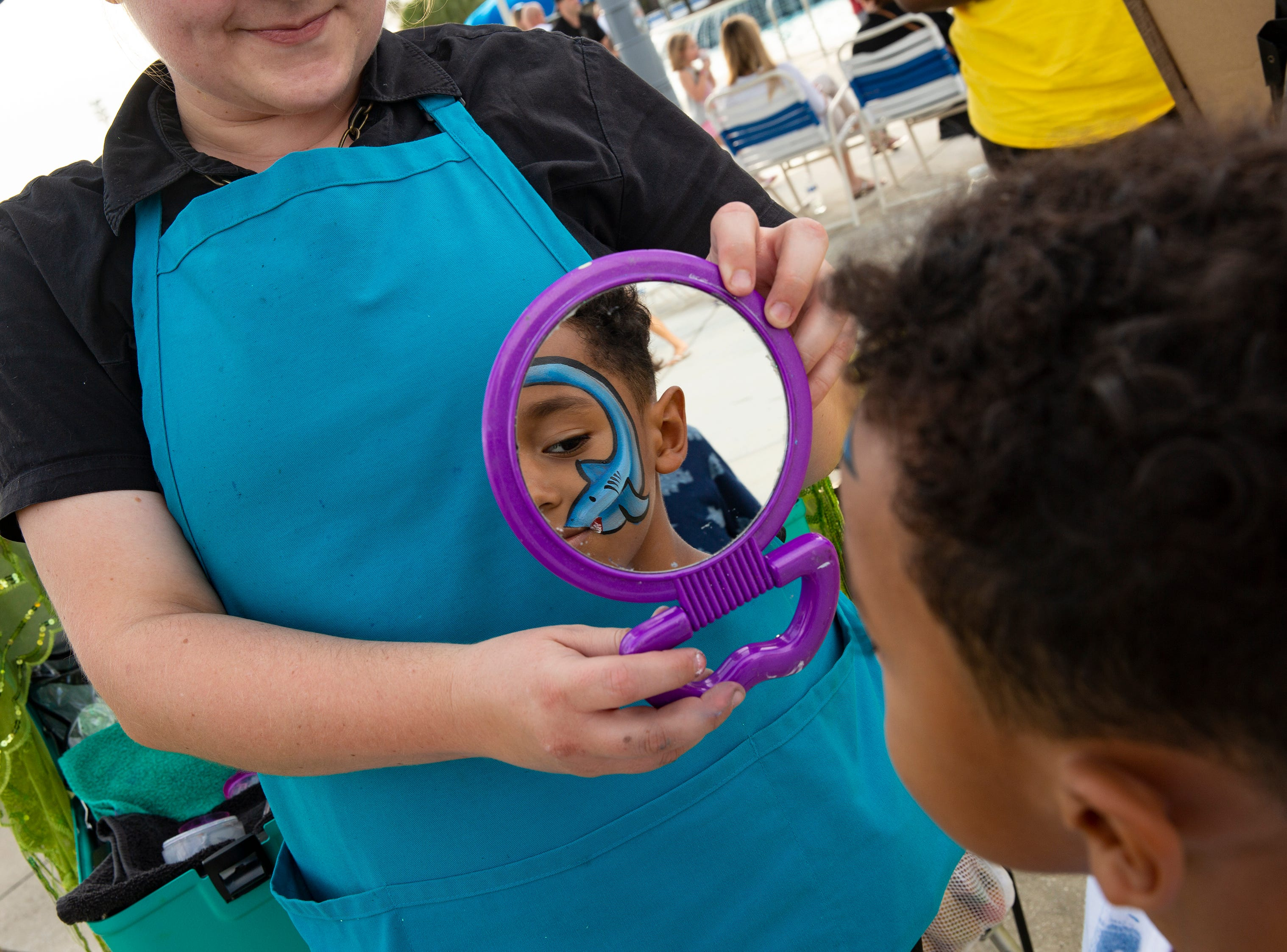 Carter Stanislaus, 5, of South Fort Myers admires his new shark face painting by Heather Payne during the Great Naples Rubber Duck Race and Water Safety Festival on Saturday, Feb. 2, 2019, at the Sun-N-Fun Lagoon in East Naples.