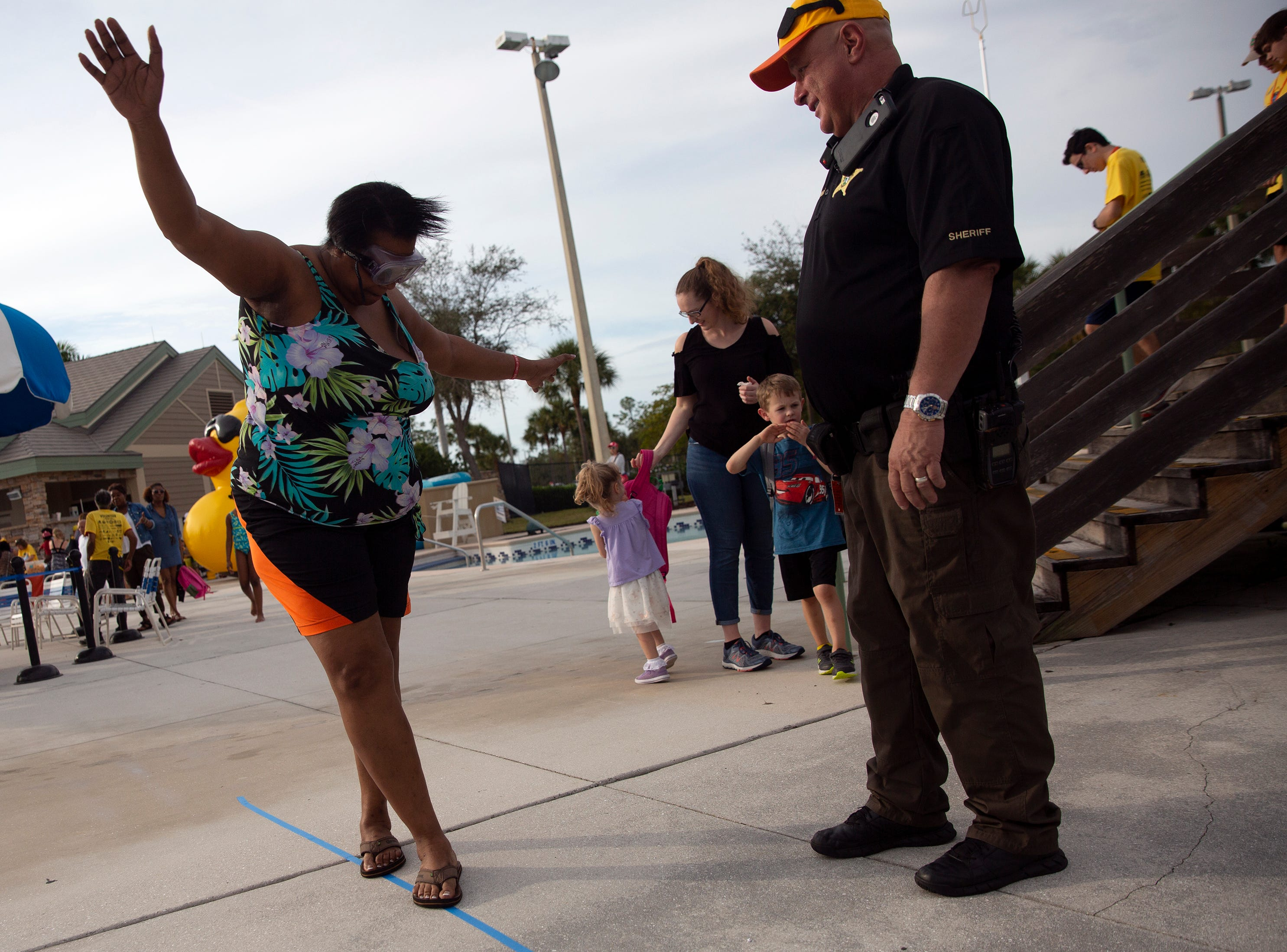 Marie Jerome attempts to walk a straight line using impairment goggles under the observation of Collier County Sheriff's Cpl. Jim Klewicki during the Great Naples Rubber Duck Race and Water Safety Festival on Saturday, Feb. 2, 2019, at the Sun-N-Fun Lagoon during in East Naples.