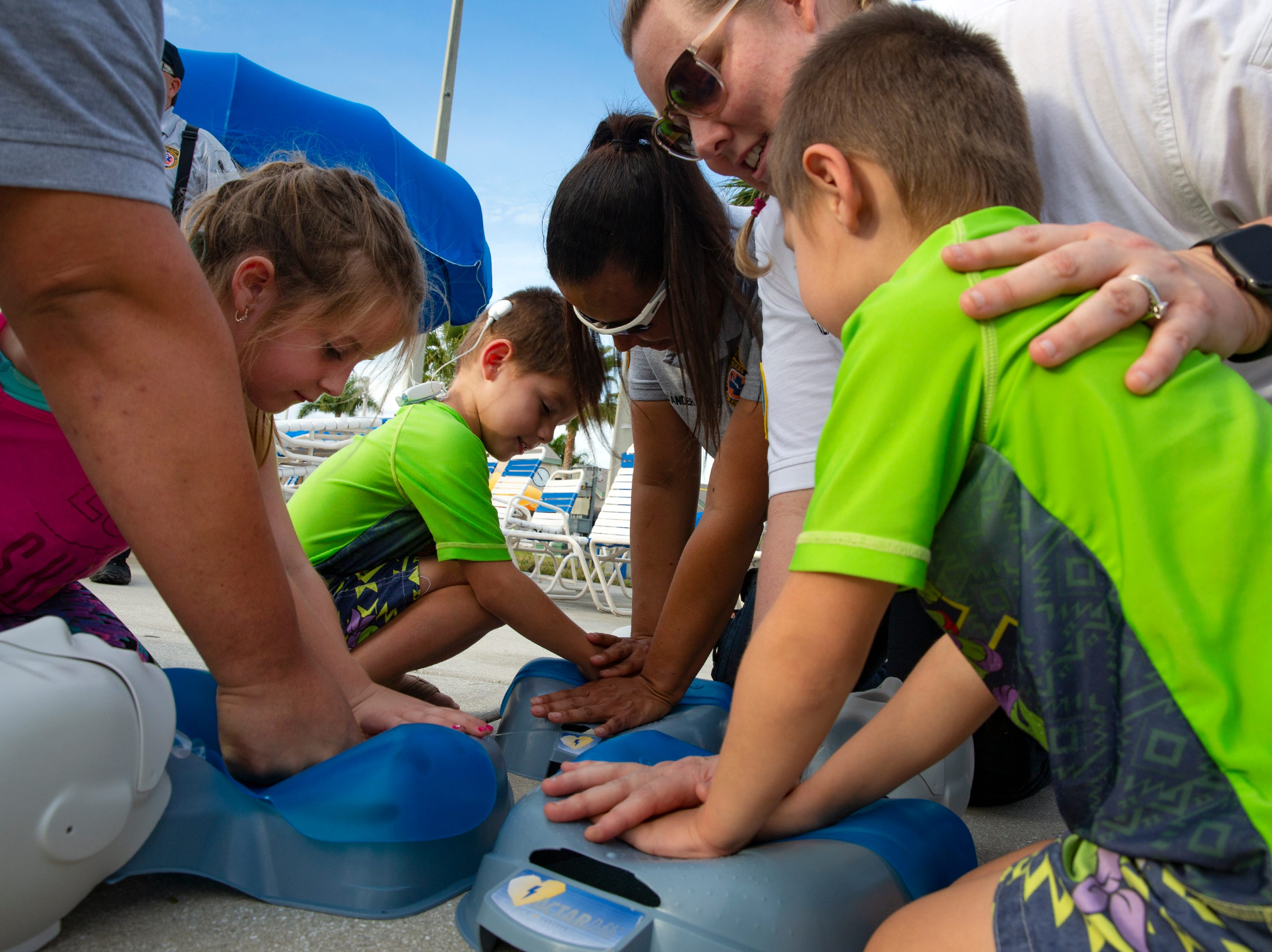 Ava Carranza, 6, from left, and her brothers Jacob Carranza, 4, and Luca Carranza, from Naples, learn CPR techniques from members of the  Collier County Emergency Medical Services during the Great Naples Rubber Duck Race and Water Safety Festival on Saturday, Feb. 2, 2019, at the Sun-N-Fun Lagoon in East Naples.