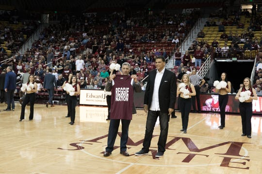"""NMSU Athletic Director Mario Moccia presents former Aggie Reggie Theus with a """"Reggie Nation""""  on Saturday at the Pan American Center."""