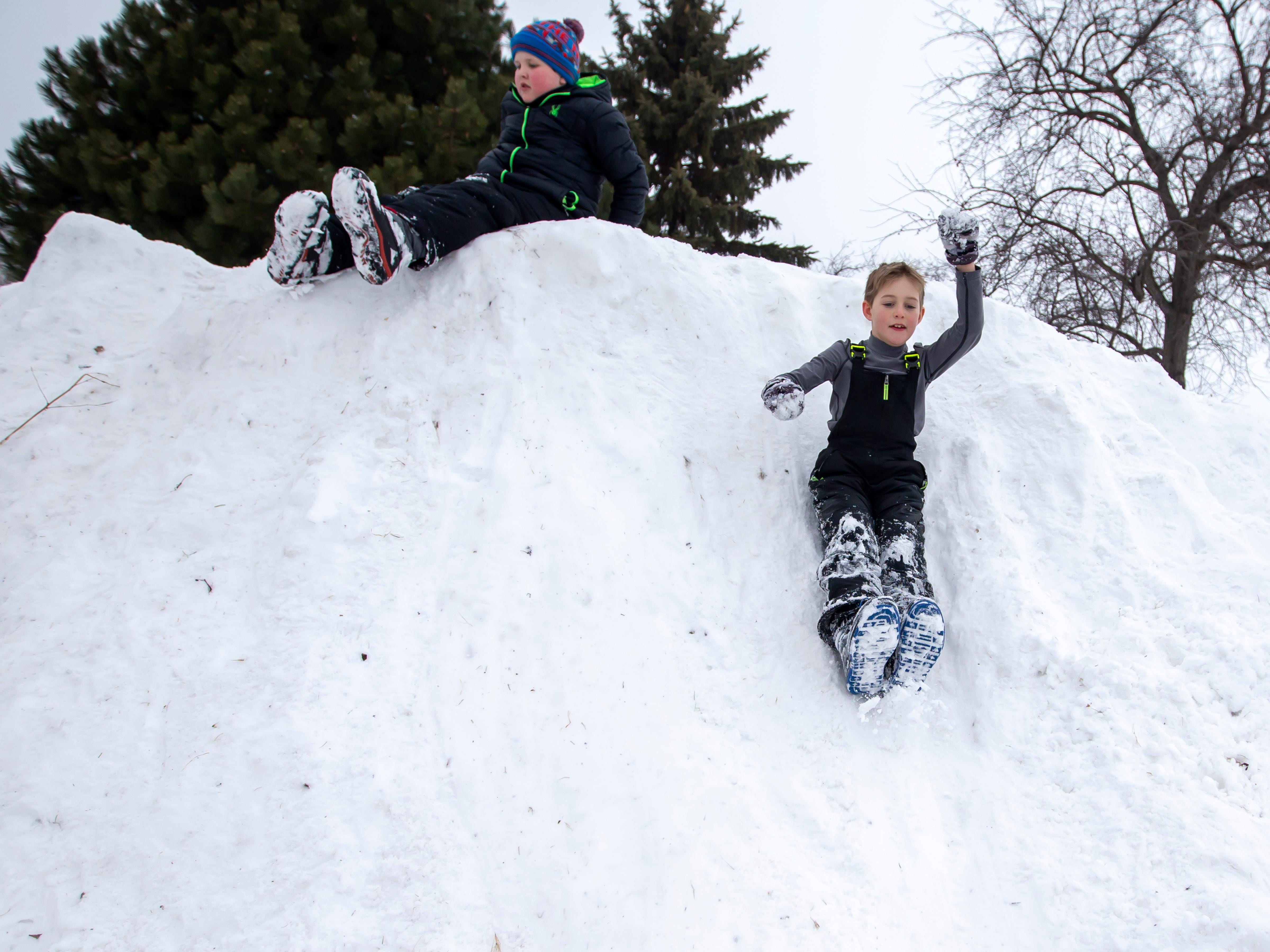 Jayden Kratzke slides down a snow pile during the Otter Street Fishing Club Winter Fisheree at Miller's Bay in Menominee Park on Saturday, Feb. 2, 2019.