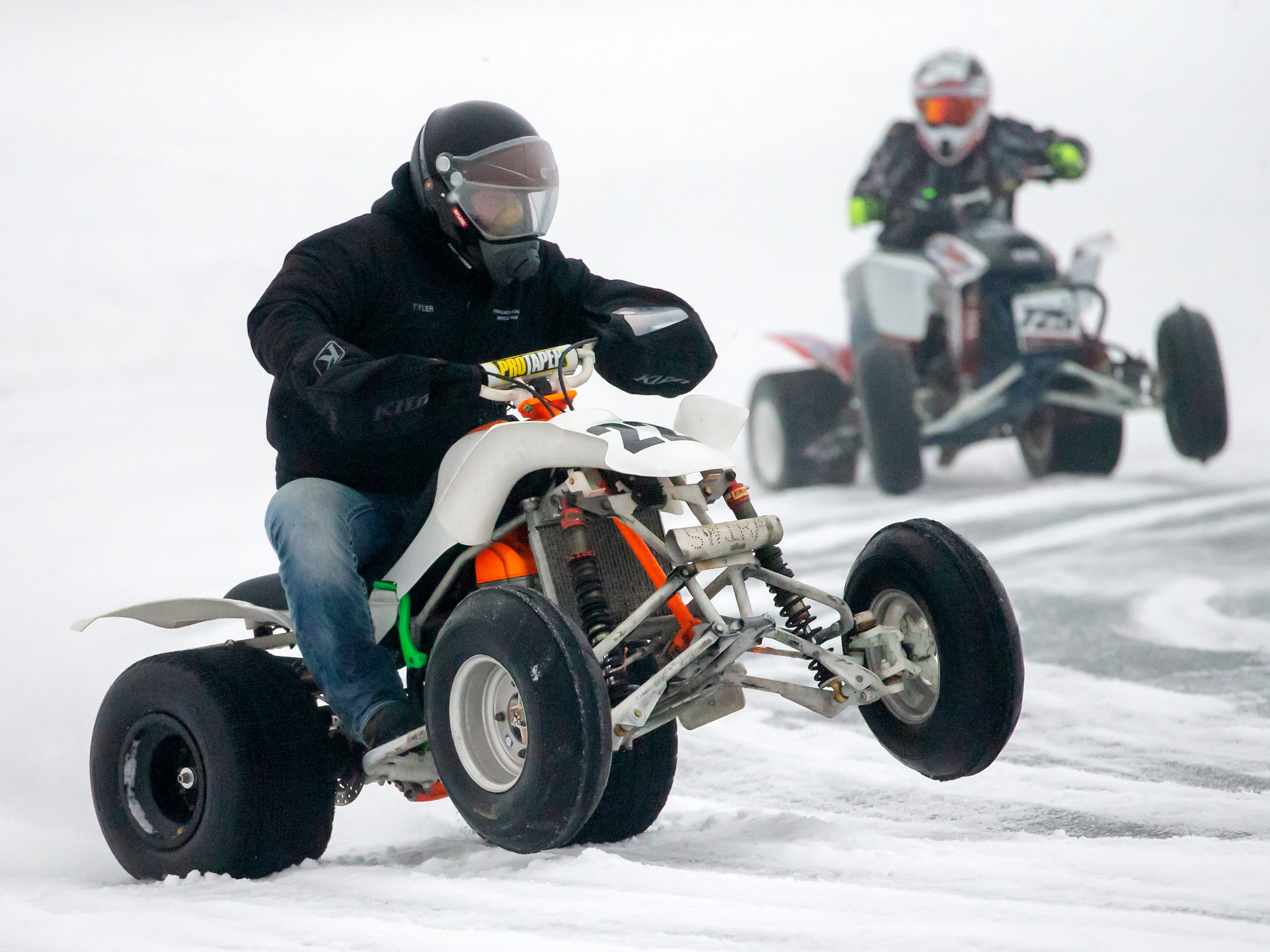 Drivers on ATVs race during the Otter Street Fishing Club Winter Fisheree at Miller's Bay in Menominee Park on Saturday, Feb. 2, 2019.