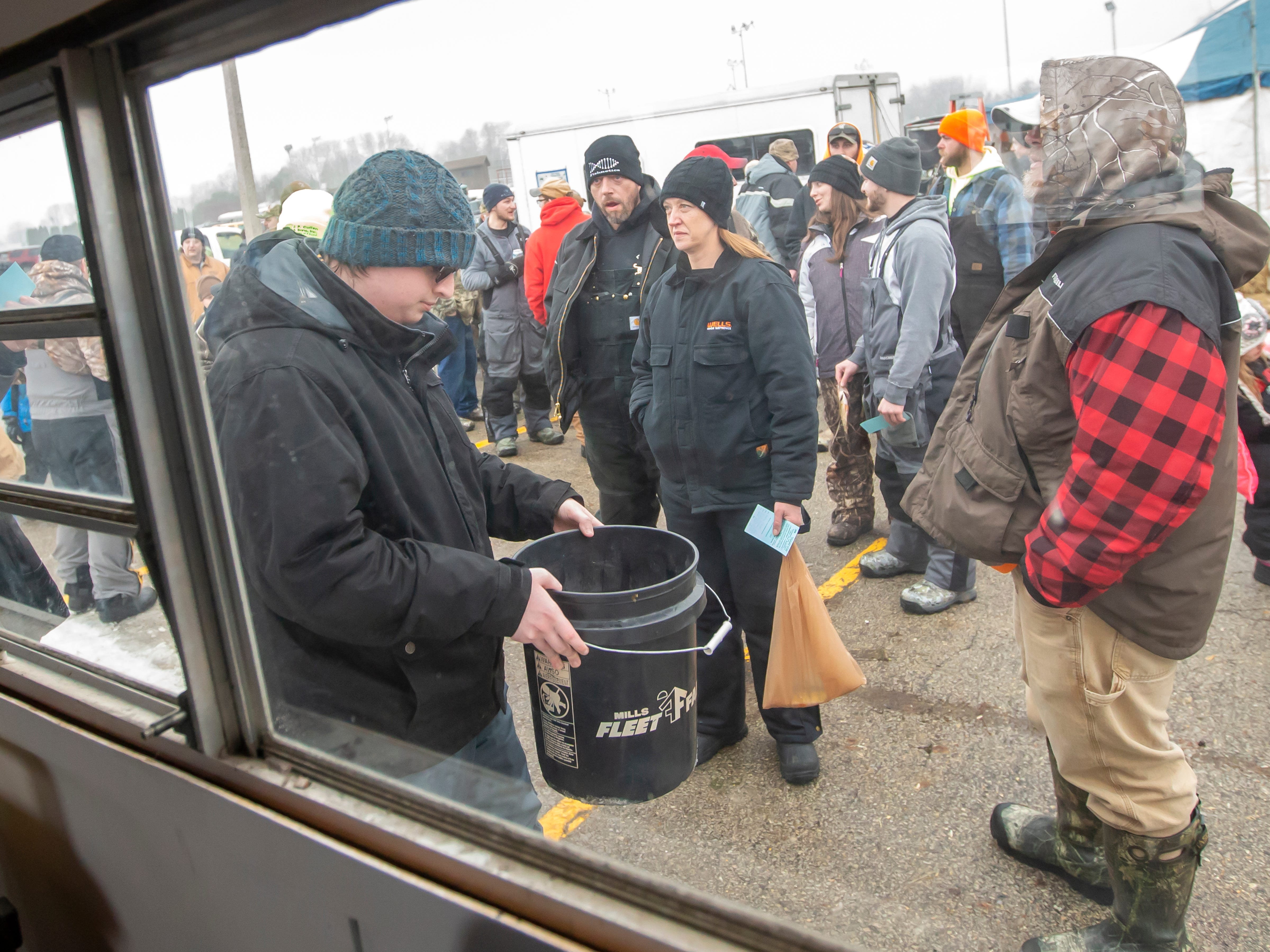People arrive with their fishing catch to enter it into the contest during the Otter Street Fishing Club Winter Fisheree at Miller's Bay in Menominee Park on Saturday, Feb. 2, 2019.