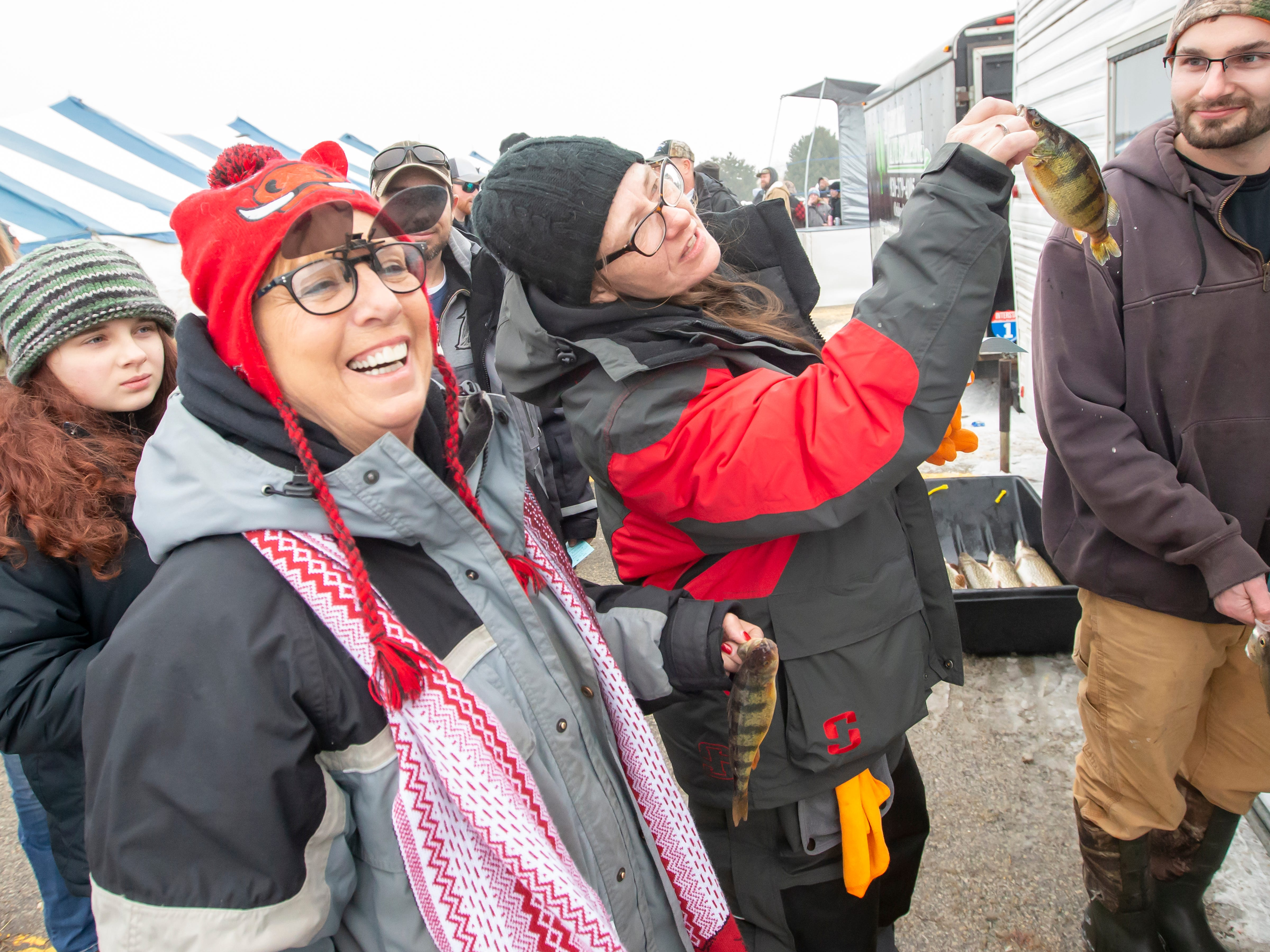 Mary and Andi Babineau wait in line to make their entry official during the Otter Street Fishing Club Winter Fisheree at Miller's Bay in Menominee Park on Saturday, Feb. 2, 2019.