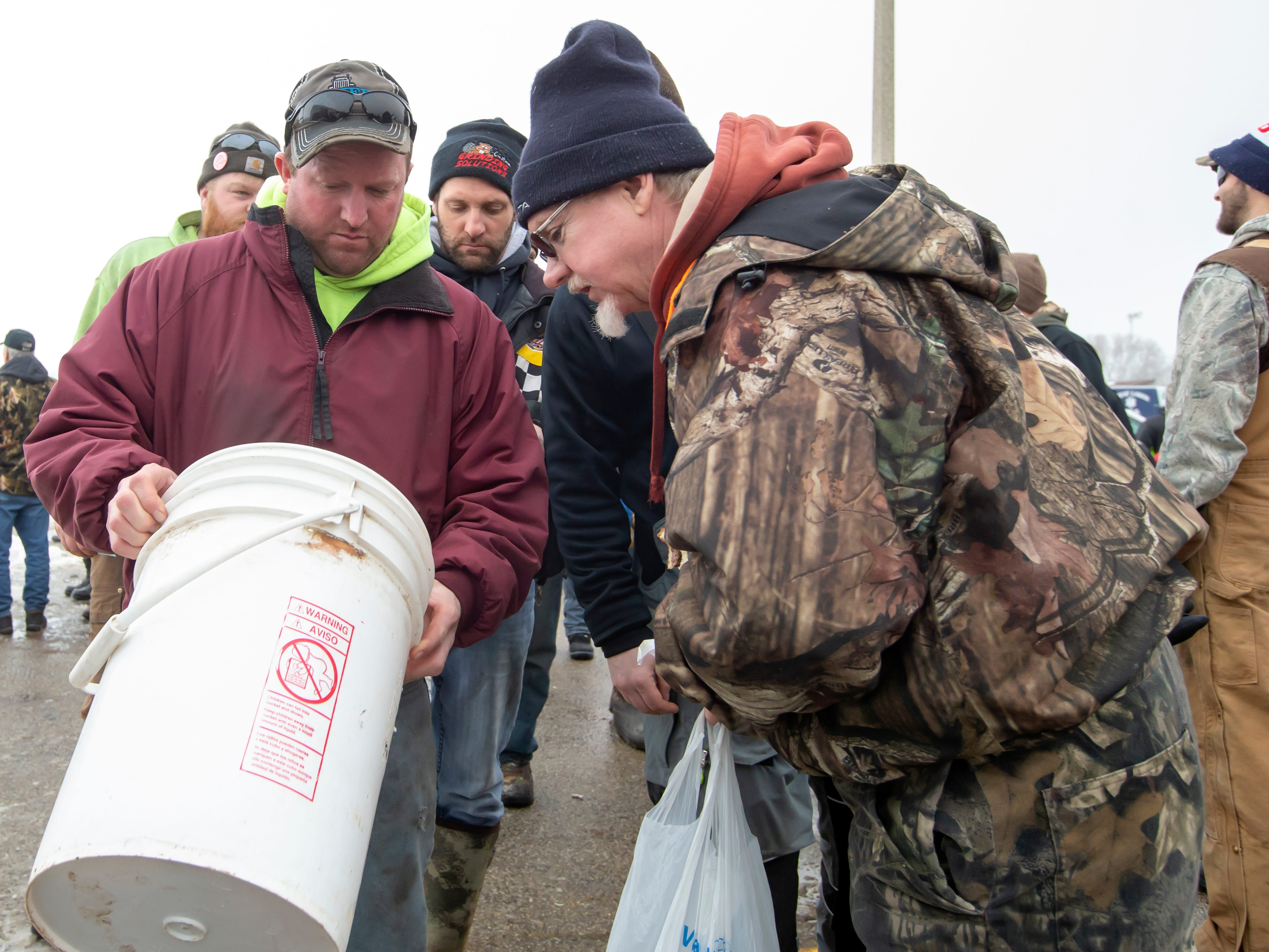 Mark Ecker shows an onlooker his white bass and perch catch waiting in the weigh-in line during the Otter Street Fishing Club Winter Fisheree at Miller's Bay in Menominee Park on Saturday, Feb. 2, 2019.