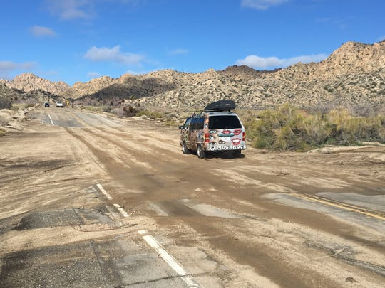 A vehicle heads north on Pioneertown Road in an area intersecting a wash. Saturday's storm left debris on portions of the road, but Pioneertown remained open Sunday.