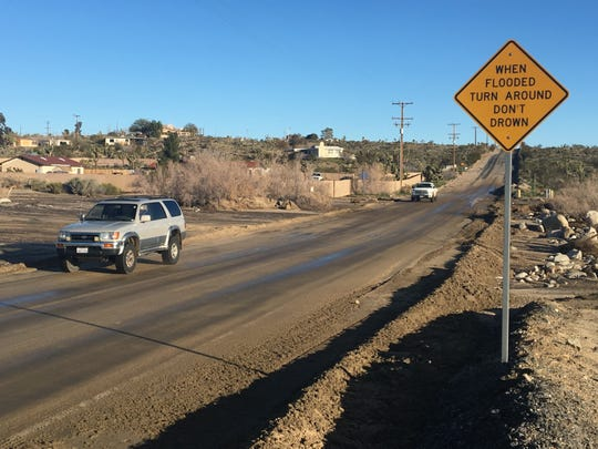 A car travels along Yucca Mesa Road in Yucca Valley.