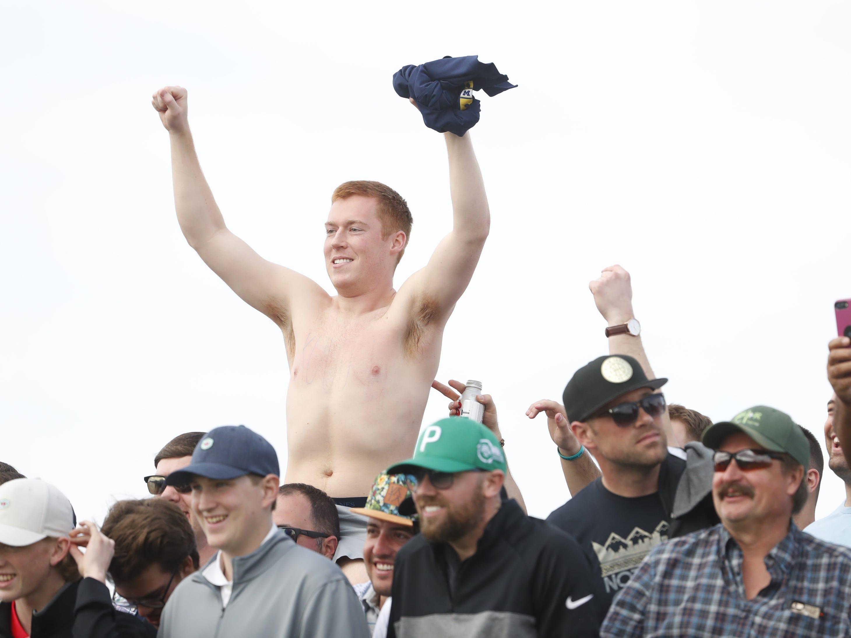 A fan takes off his shirt as Rickie Fowler takes to the tee box on the 15th hole during the third round of the Waste Management Phoenix Open at TPC Scottsdale in Scottsdale, Ariz. on February 2, 2019.