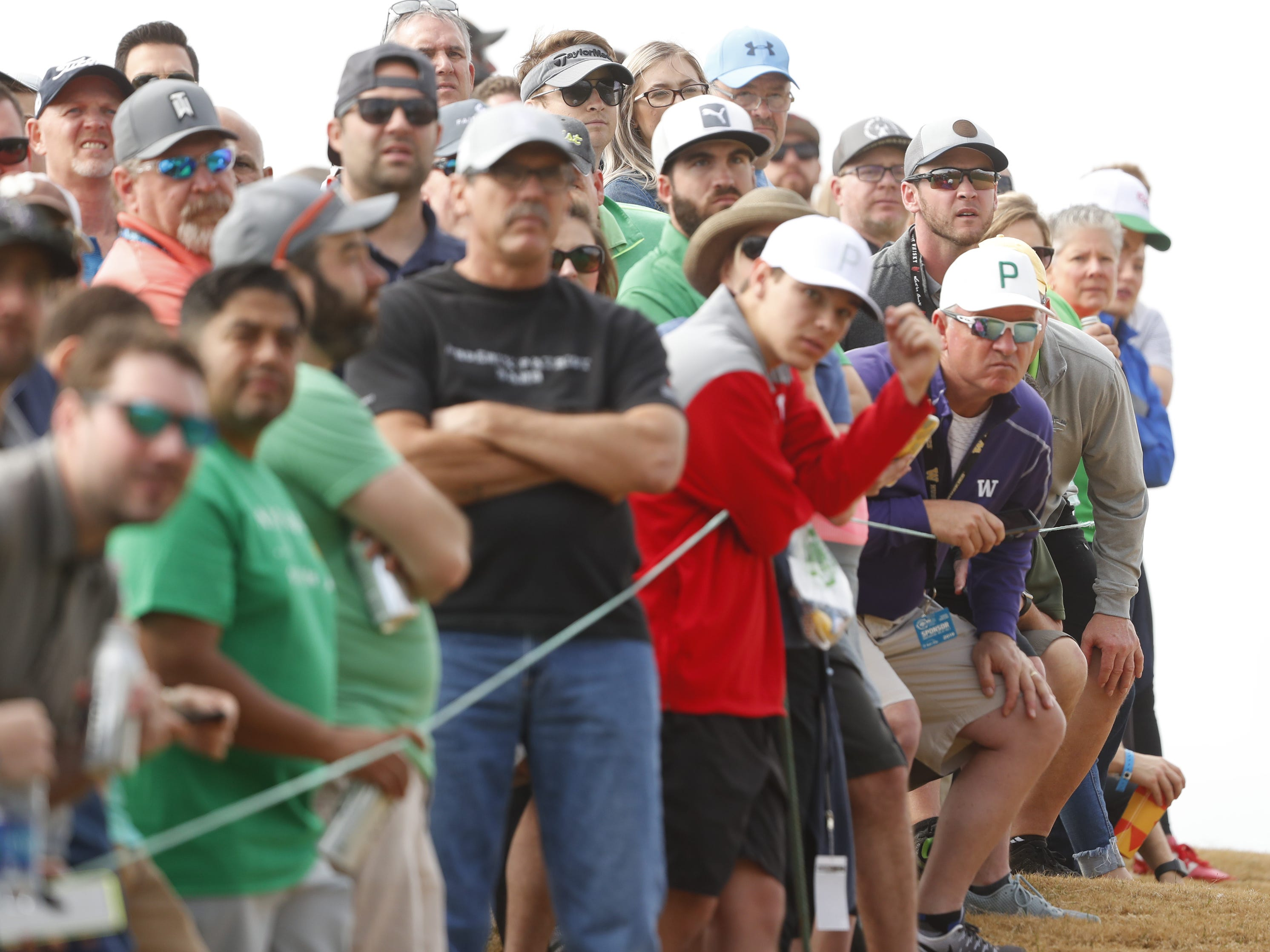 Fans watch Rickie Fowler's shot from the 9th hole fairway during the third round of the Waste Management Phoenix Open at TPC Scottsdale in Scottsdale, Ariz. on February 2, 2019.