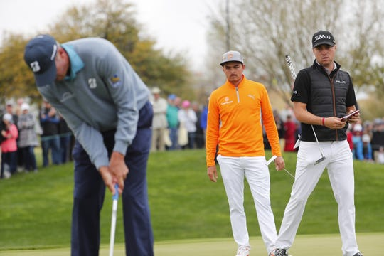 Matt Kuchar putts on the eighth hole wile Rickie Fowler and Justin Thomas Watch during the final round of the Waste Management Phoenix Open at the TPC Scottsdale Feb. 3, 2019.