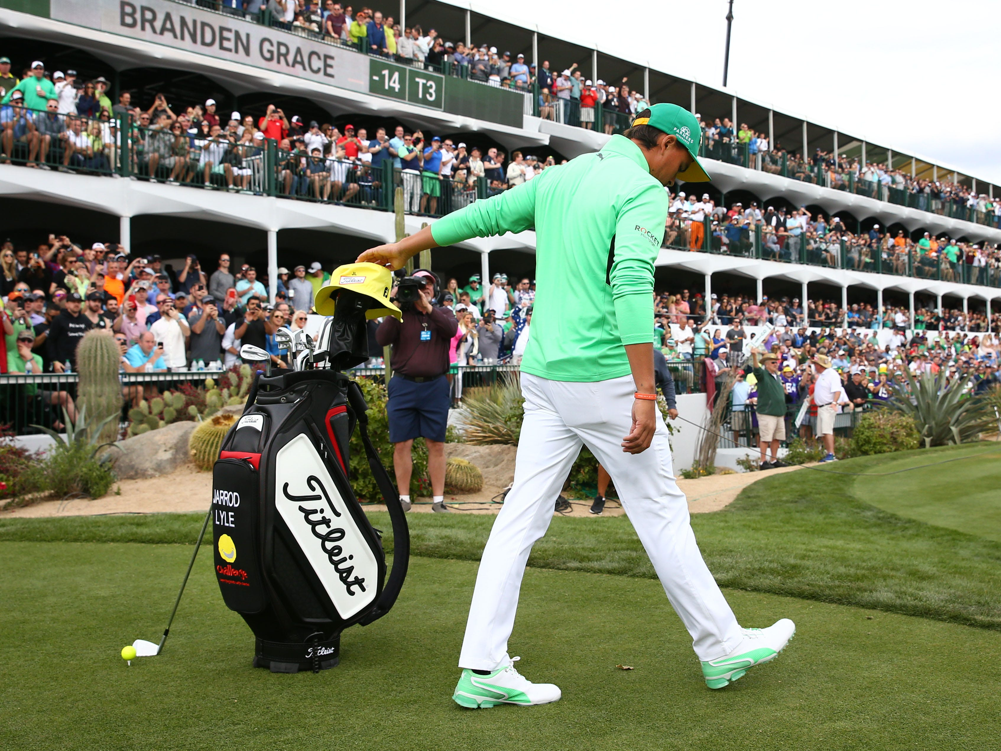 Rickie Fowler reaches out and touches the yellow hat to pay tribute at late Jarrod Lyle, who died last summer from leukemiaduring third round action on the 16th hole on Feb. 2 during the Waste Management Phoenix Open at the TPC Scottsdale Stadium Course.