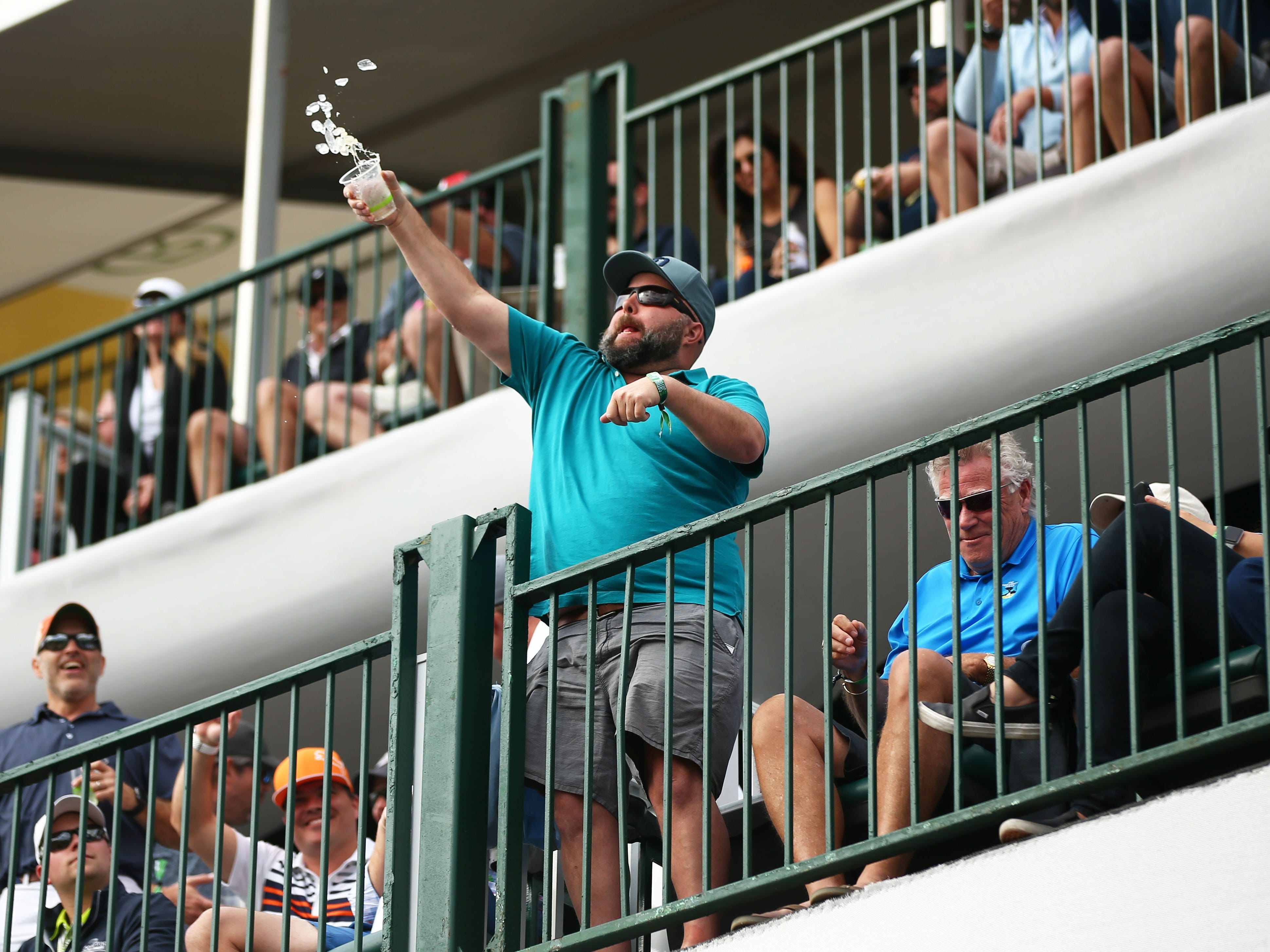 A spectator tosses his ice into the crowd below on the 16th hole during third round action on Feb. 2 during the Waste Management Phoenix Open at the TPC Scottsdale Stadium Course.