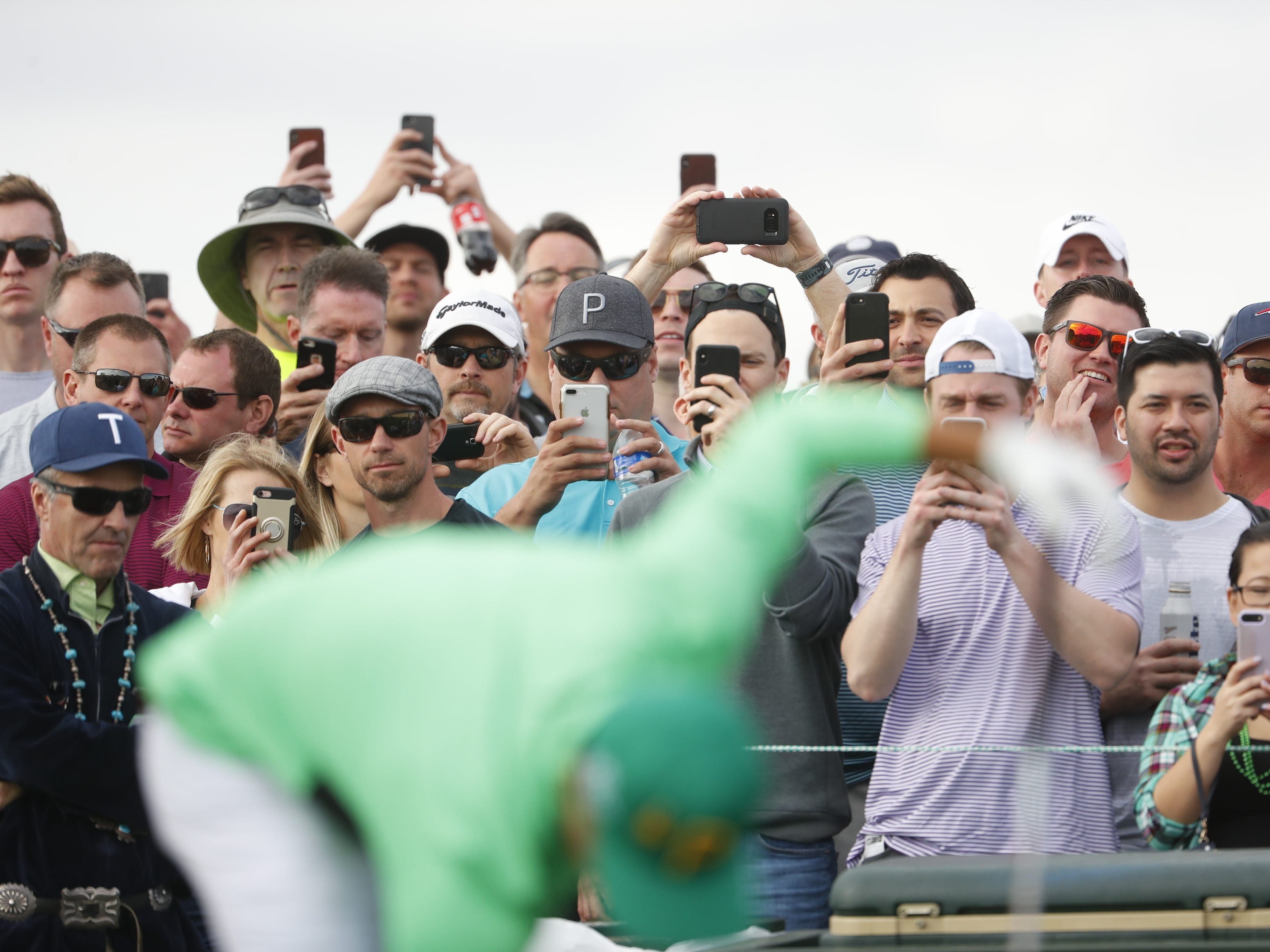 Fans take out their phones to video Rickie Fowler's tee shot on the 15th hole during the third round of the Waste Management Phoenix Open at TPC Scottsdale in Scottsdale, Ariz. on February 2, 2019.