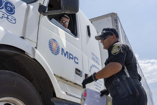 Juan Jimenez, an ADOT enforcement officer, inspects Francisco Bustamante's truck at the ADOT Nogales facility.
