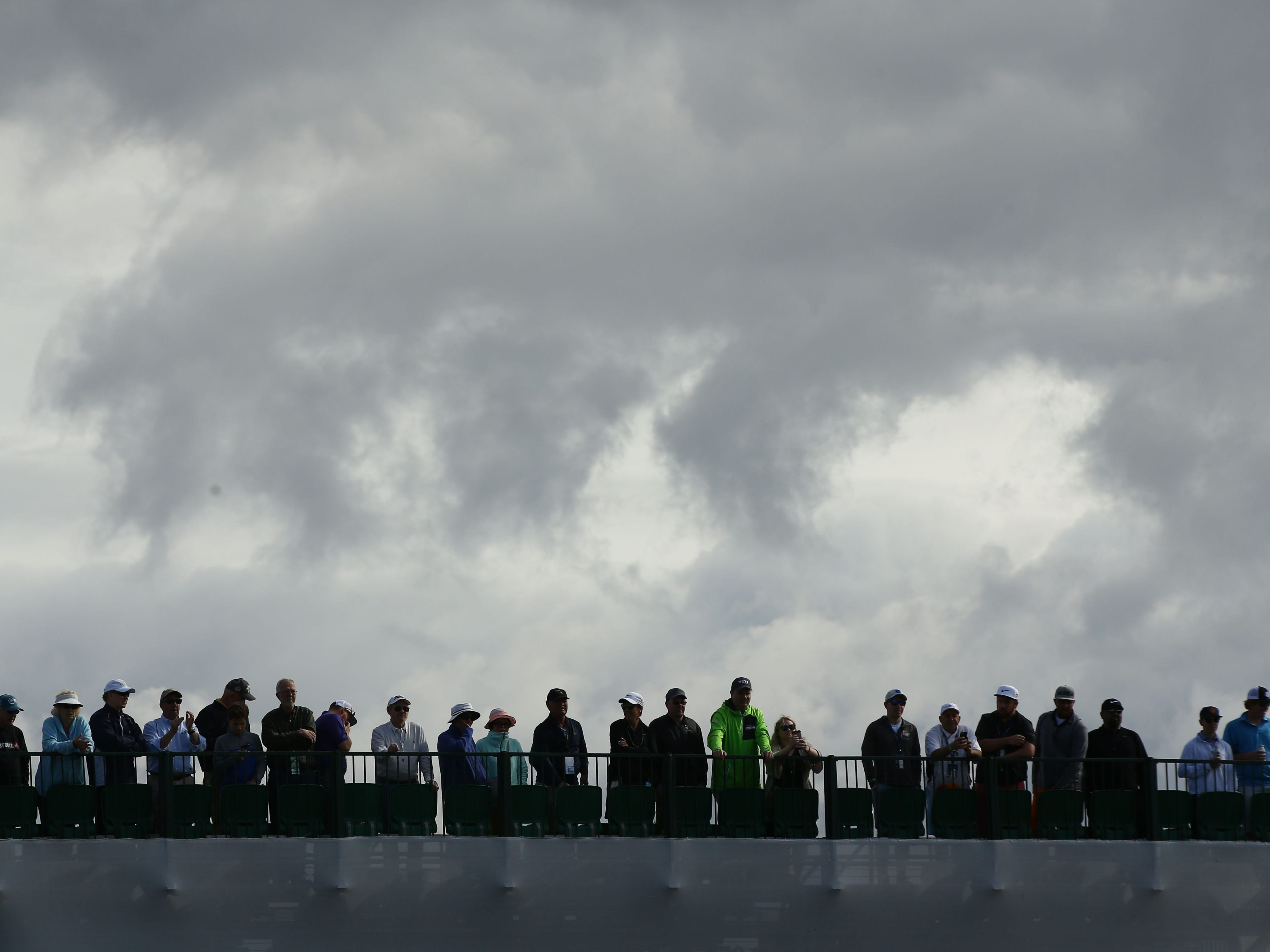 Spectators watch Rickie Fowler putt on the 2nd hole during third round action on Feb. 2 during the Waste Management Phoenix Open at the TPC Scottsdale Stadium Course.