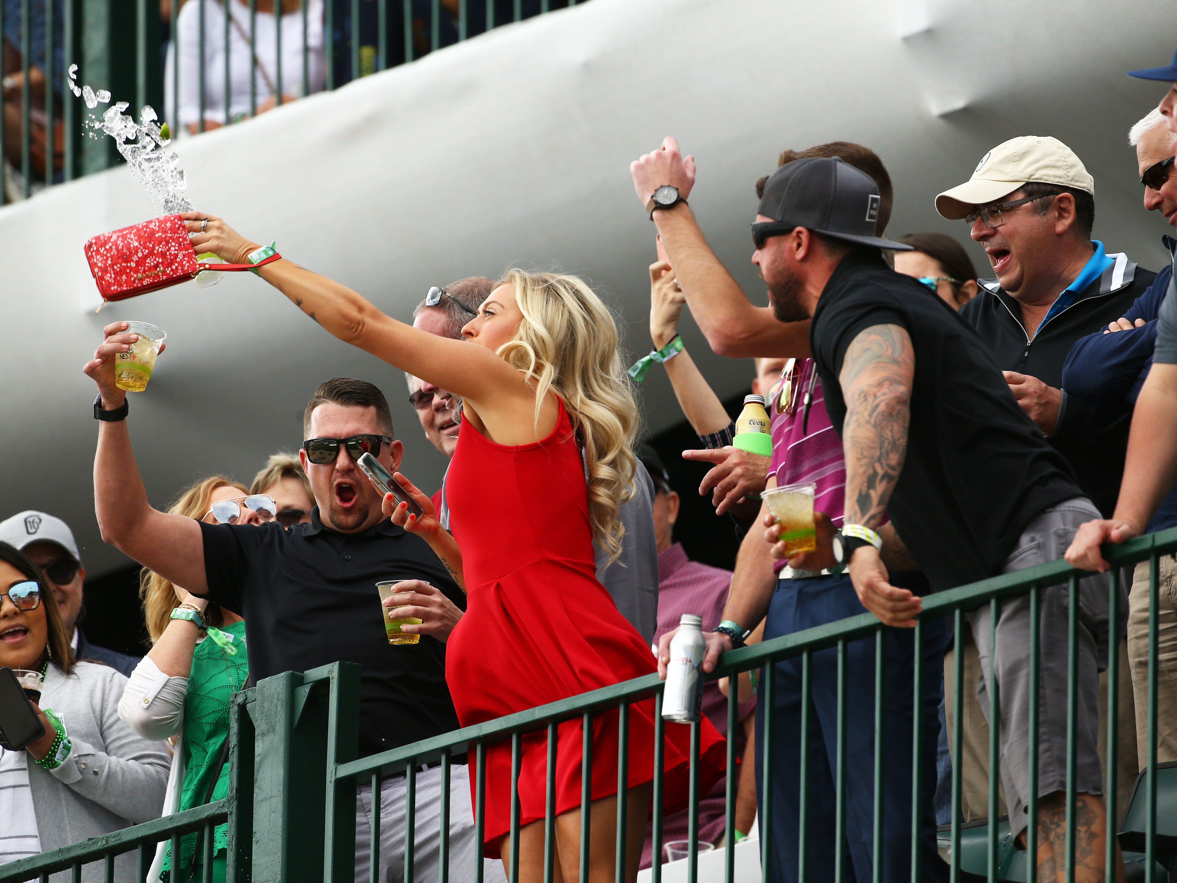 After downing a drink, a woman tosses the ice into the crowd below on the 16th hole during third round action on Feb. 2 during the Waste Management Phoenix Open at the TPC Scottsdale Stadium Course.