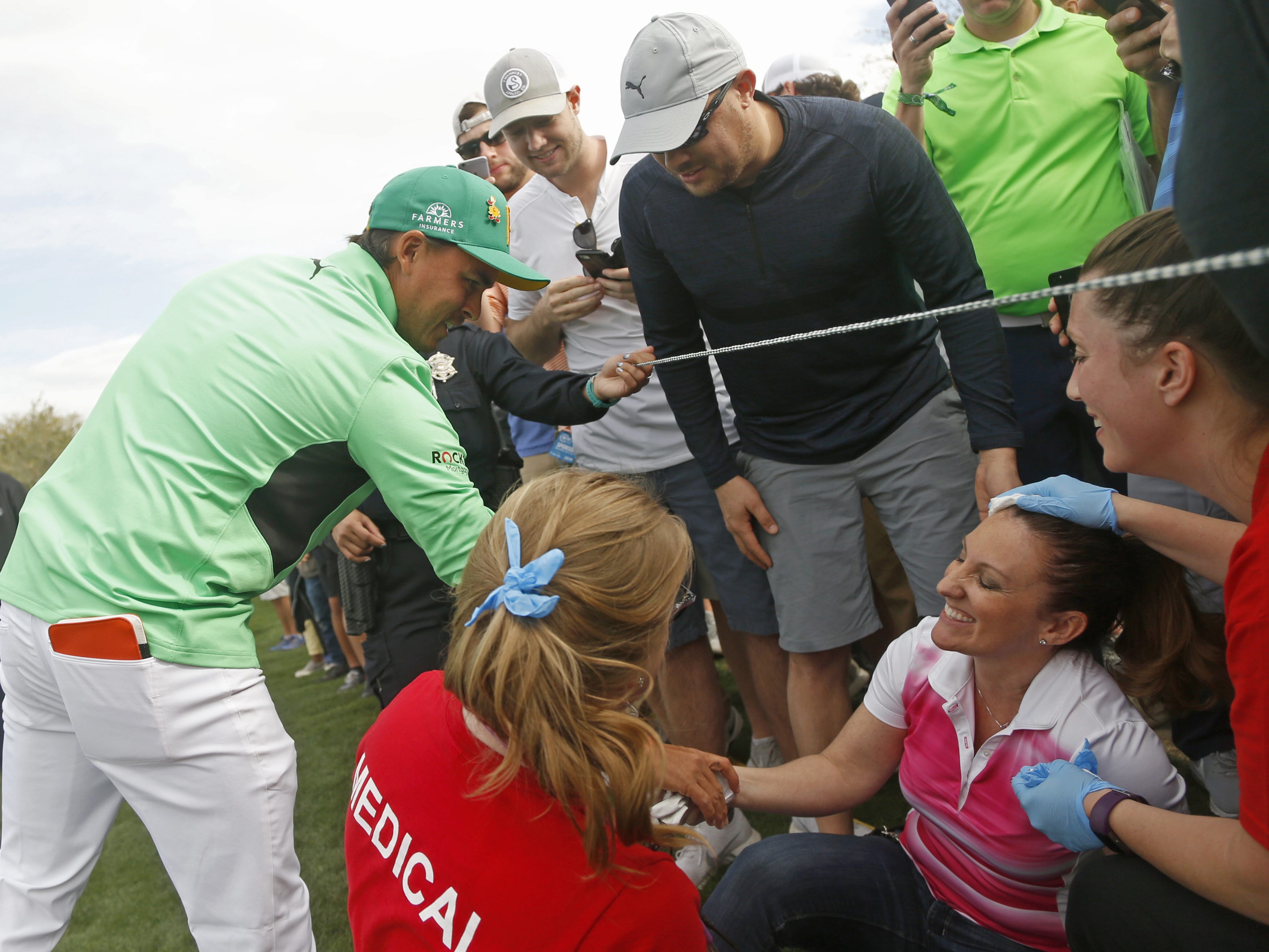 Rickie Fowler gives a glove to a fan who was hit with his ball in the head on the 15th hole during the third round of the Waste Management Phoenix Open at TPC Scottsdale in Scottsdale, Ariz. on February 2, 2019.